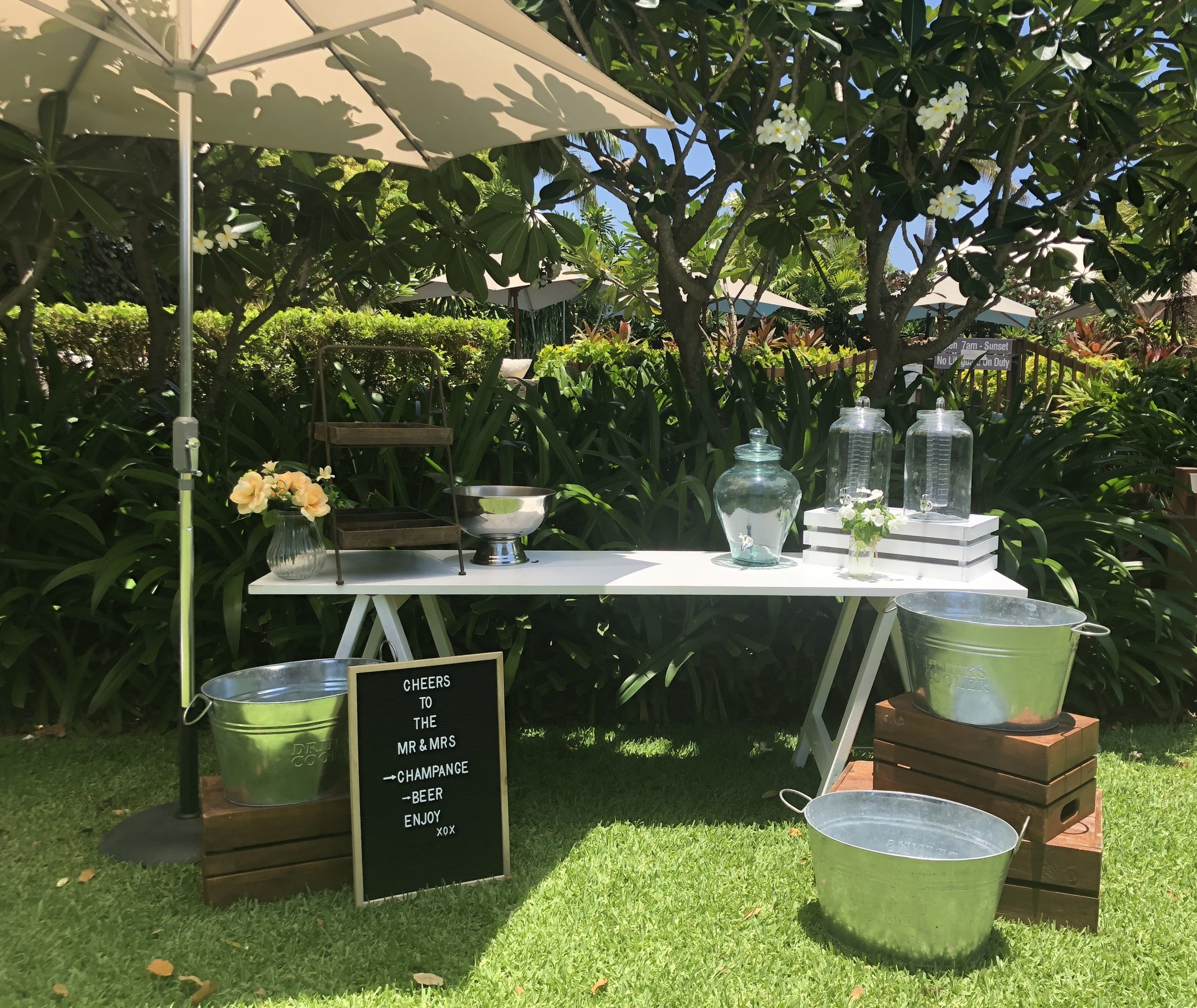 White wooden trestle table bar: $220 - Just add your favourite drinks and ice. Includes:White wooden tableX3 Metal tubsX4 CratesX3 Drink dispensersDrink stand or trayMarket umbrellaChampagne bowlLetterboard