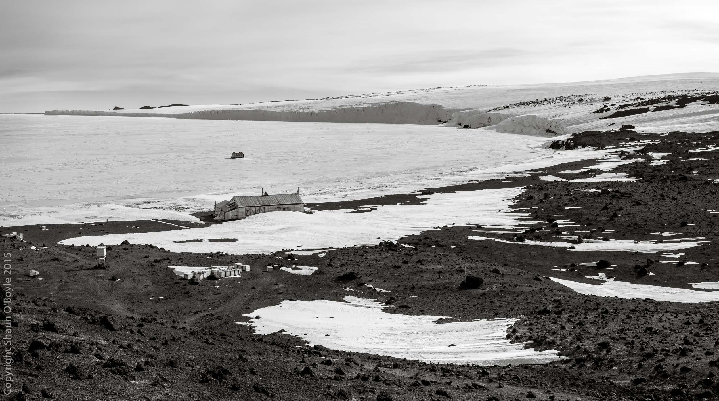 Cape Evans Hut and Barne Glacier. The fish hut on the sea ice is used for scuba diving and collecting samples and specimens from McMurdo Sound.
