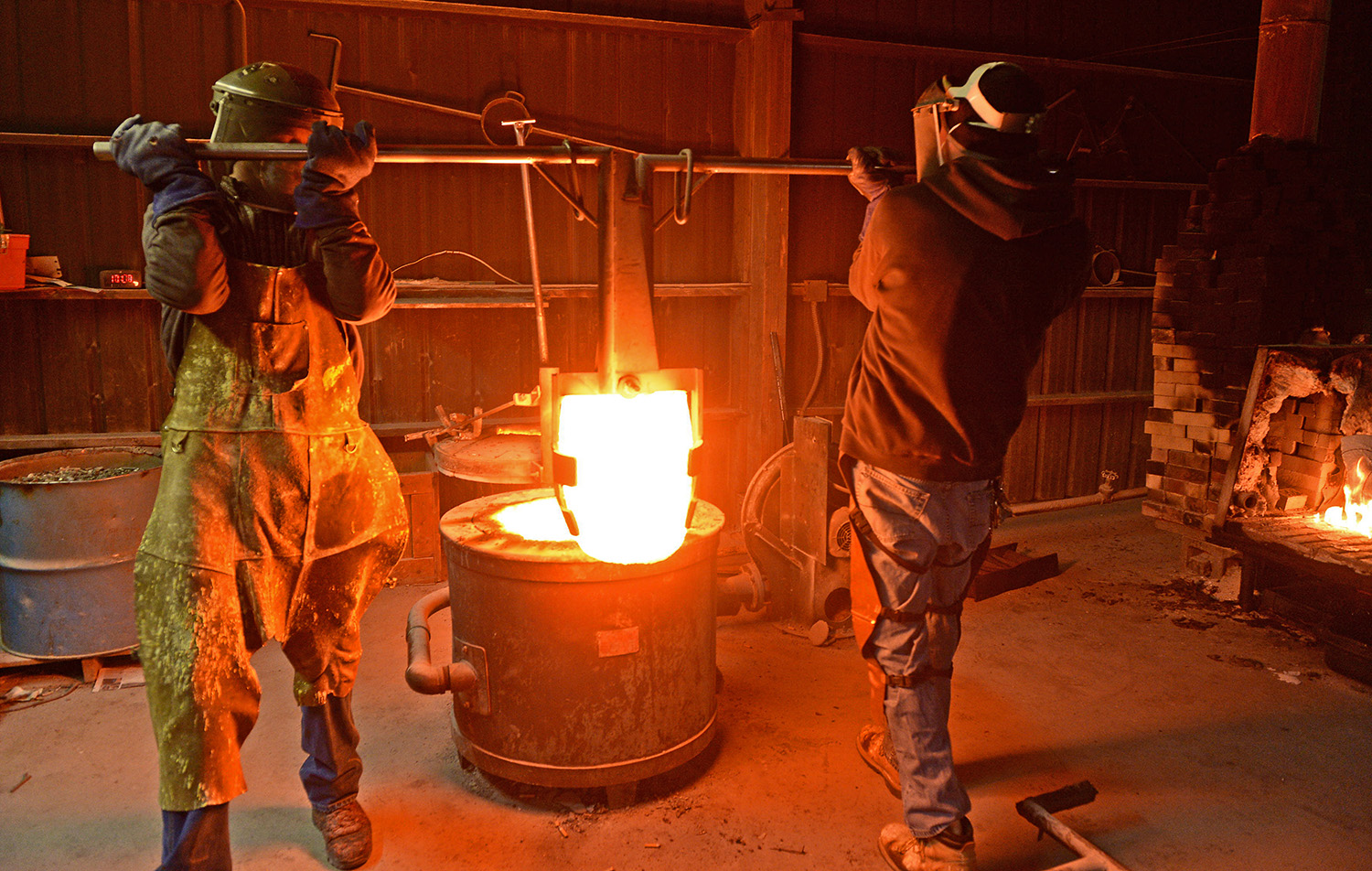 Melting pot: - The only material that can withstand the heat and contain the molten metal is graphite. The liquid bronze is in a graphite crucible which is handled by a giant pair of steel lifting tongs, then placed into a set of pouring shanks.