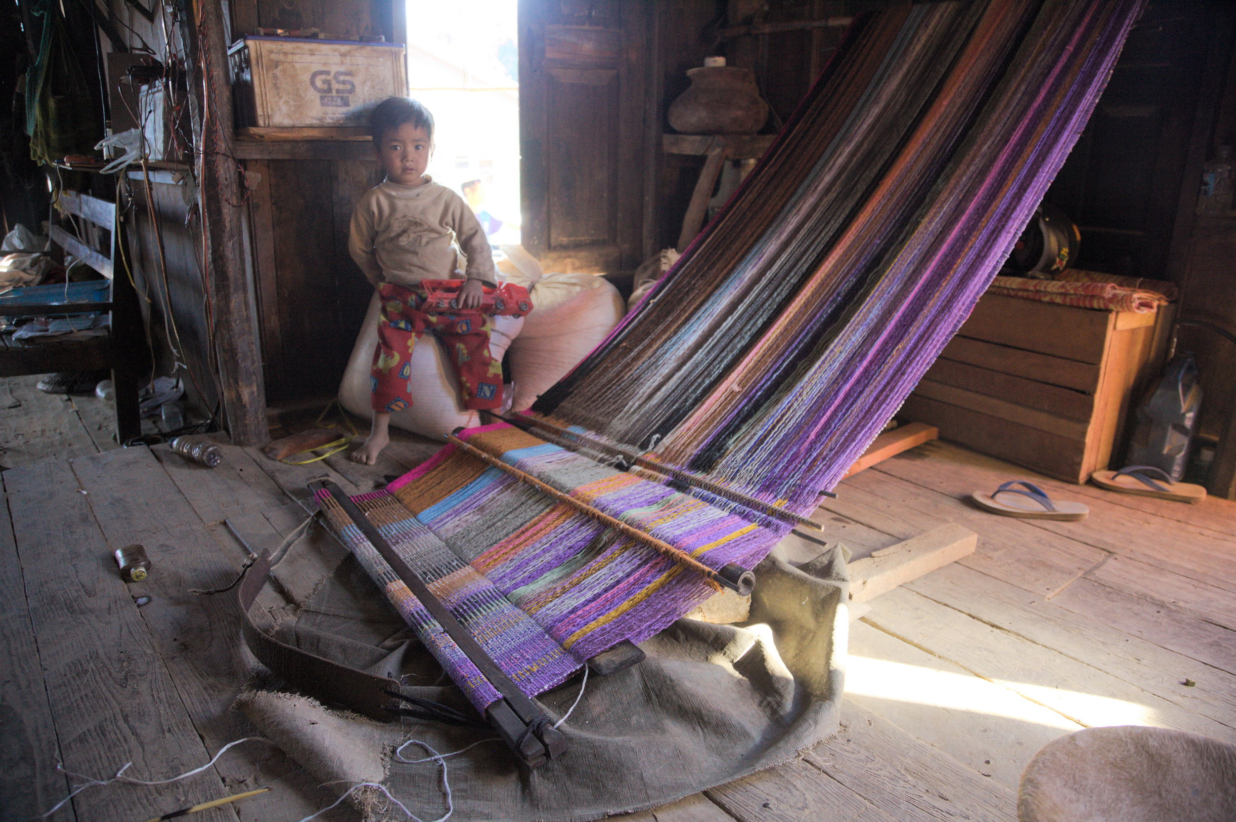A child next to a back-strap loom in Tiddim, Chin State