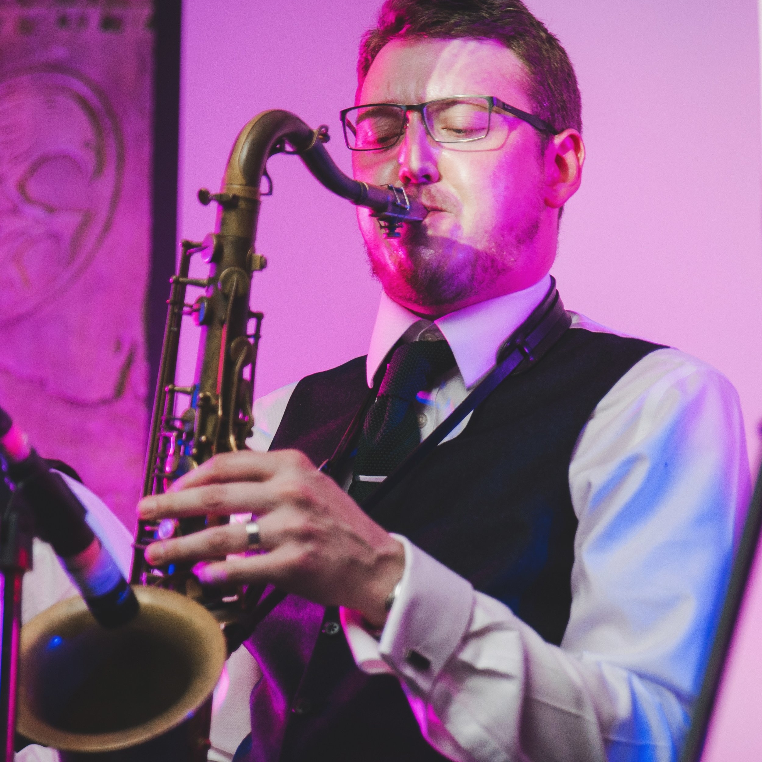 """John Mckillup - Saxophone, keyboards, percussion and backing vocalsSince graduating from the prestigious Jazz degree course at Leeds College of Music course and with an ALCM in Jazz Performance, John moved from Newcastle Upon Tyne to the bright lights of London.Since 2013, John has established himself as the go-to young saxophone player having already played alongside big-names such as Wynton Marsalis, Tim Garland, Bill Bruford, Gary Husband and The Average White Band's Steve Ferrone.John joined The Dark Blues in 2015 but continues to perform across the globe with various jazz outfits and as an artist in his own right. He's even been known to throw in the odd rap as part of his stint with The Dark Blues!Favourite Dark Blues party song: """"Don't stop me now"""" by Queen – """"As soon as Lol sings the first words, everyone on the dance floor goes crazy! Plus I get to play the Brian May guitar solo on tenor sax."""""""