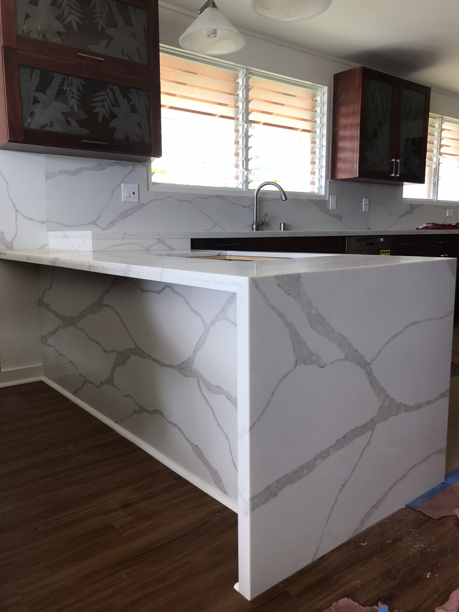 Hawaii Kai Residence - Kitchen counter tops with full-height back splash and wrap around stone with waterfall on peninsula. Veins bookmarked for pattern continuity.