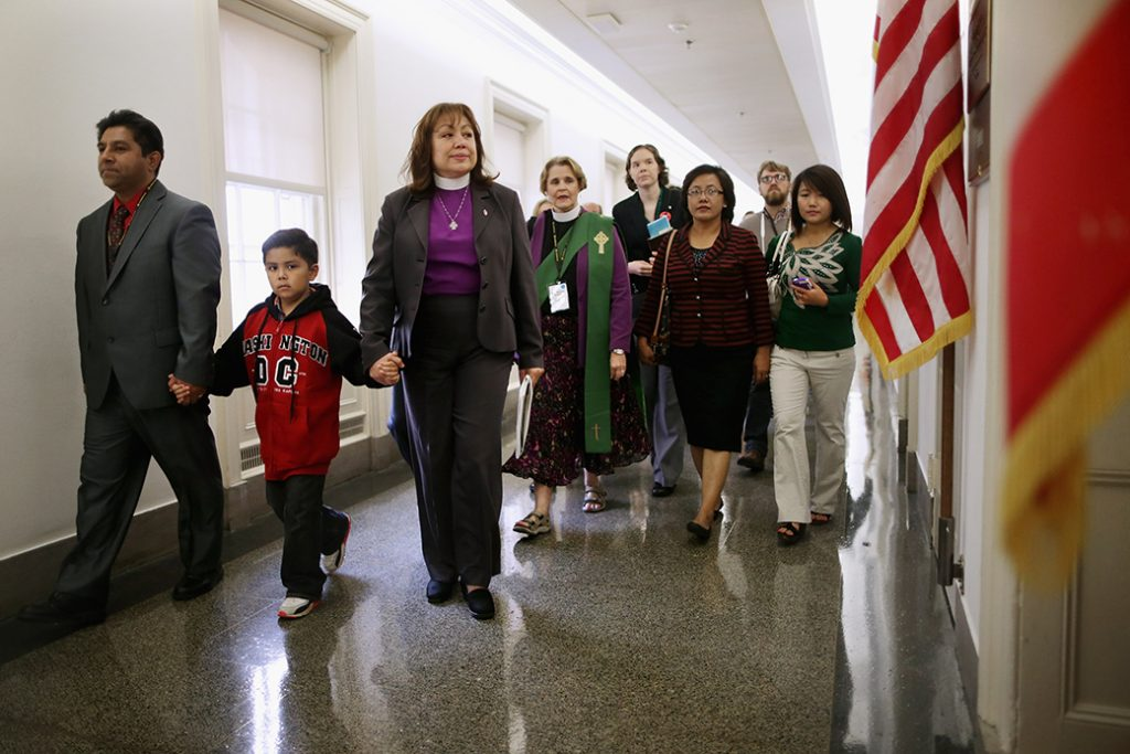 Led by Bishop Minerva Carcaño (third from left), a father and son join people from various Christian denominations at the constituent office of former Speaker of the House John Boehner (R-OH) while lobbying for immigration reform on Capitol Hill, October 8, 2013, in Washington. (GettyChip Somodevilla)