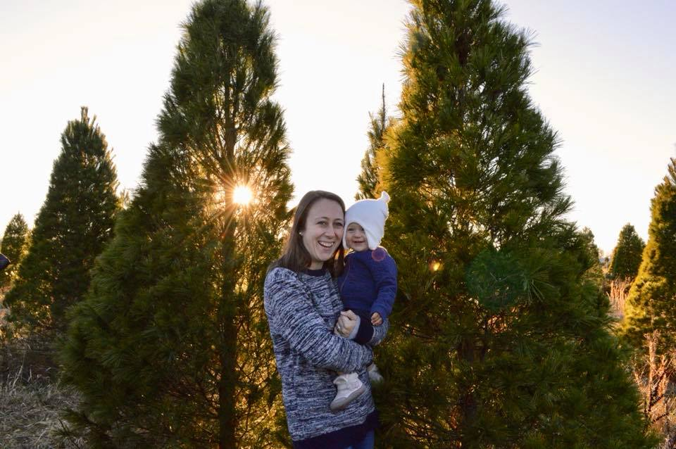 Mom and baby at a Christmas tree cutting lot