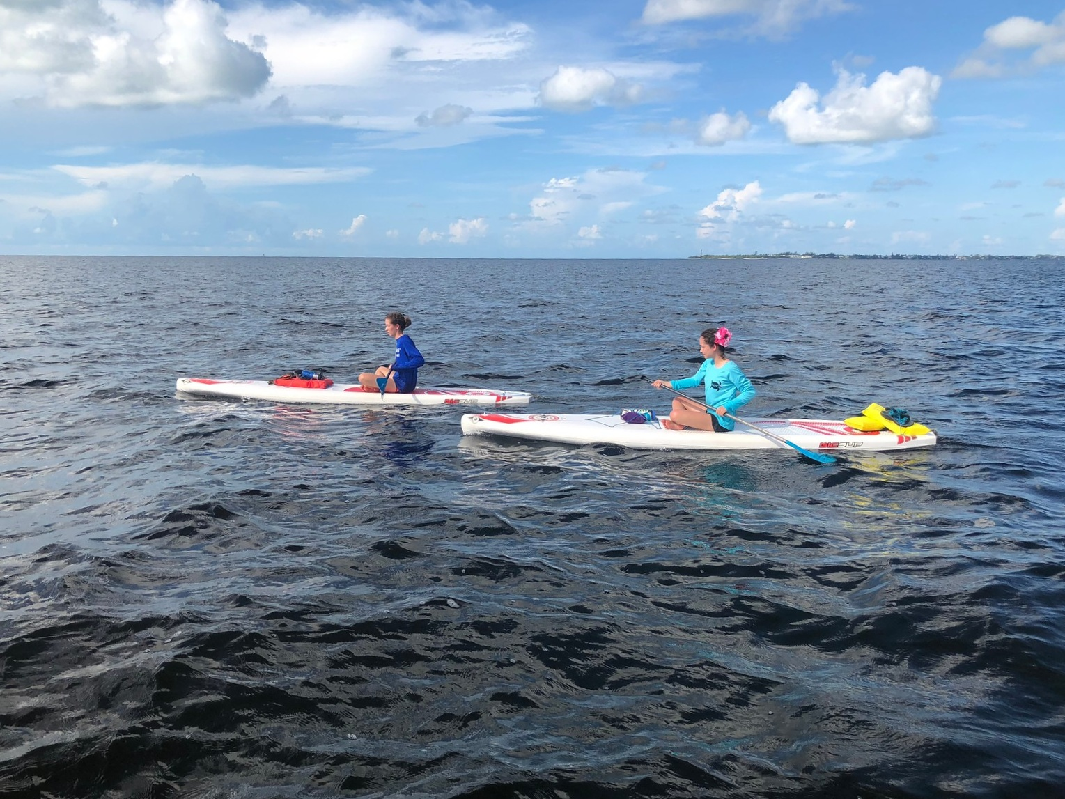 Sitting or kneeling on your board can reduce resistance when paddling in strong winds.
