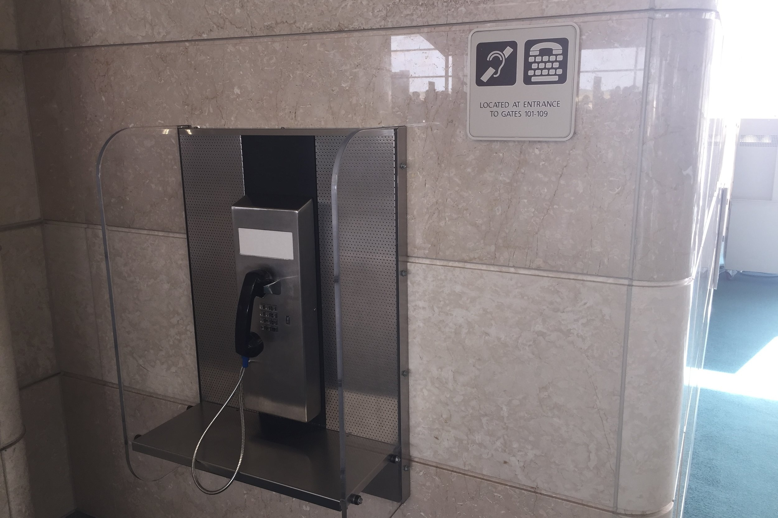 Courtesy Telephone in Orlando Airport with sign for ADA phone installation
