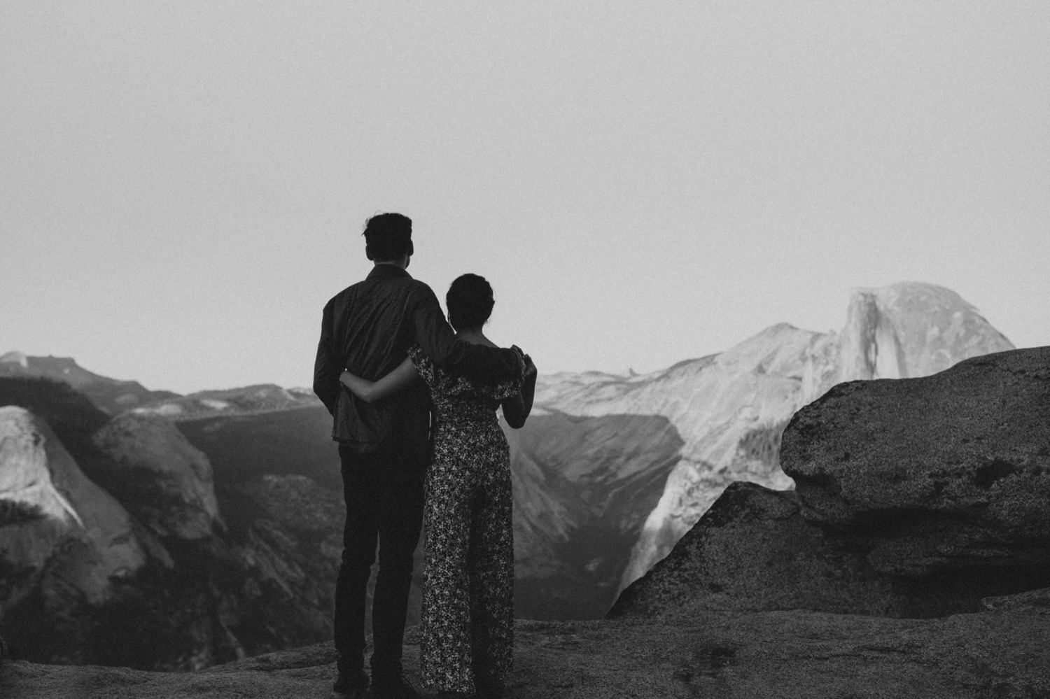 Couple standing in front of Half Dome at Glacier Point in Yosemite National Park
