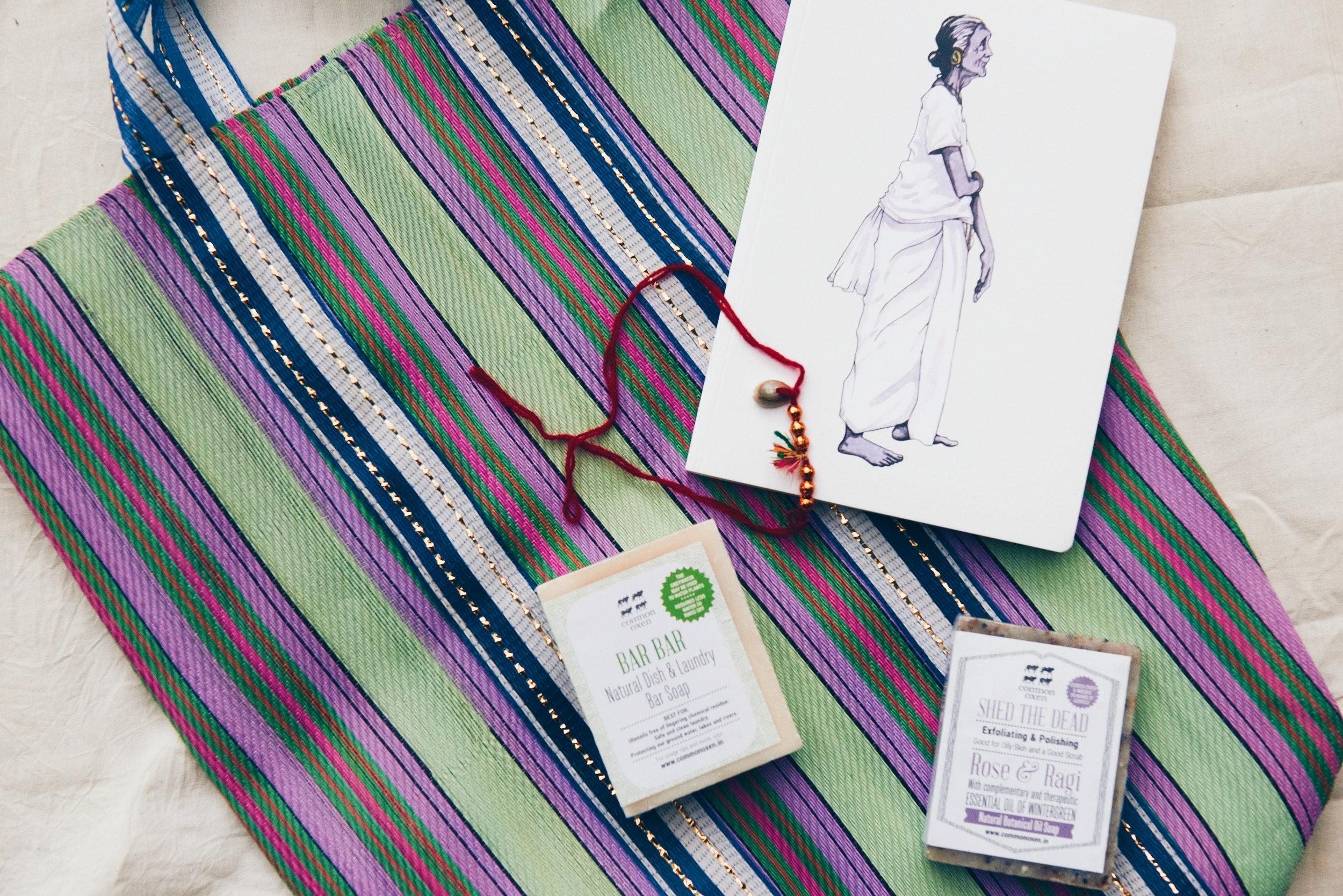 An Indian tote, soaps, Kalonji seeds, a notebook, Rakhi bracelet, and recipes