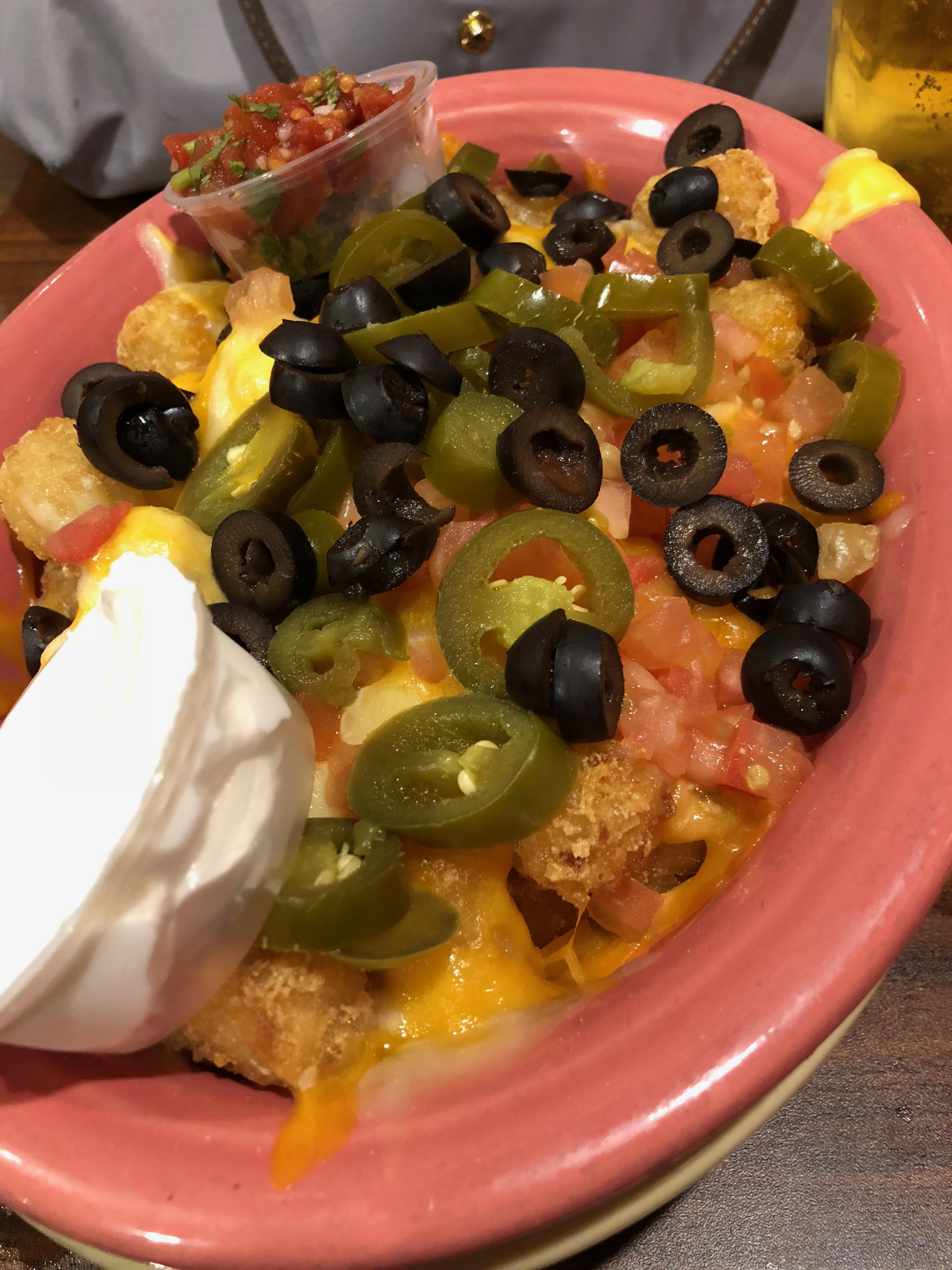 Tot-Chos - Tator tots topped with nacho cheese, jalapeños, sliced black olives, and tomatoes. Served with fresh pico de gallo and sour cream