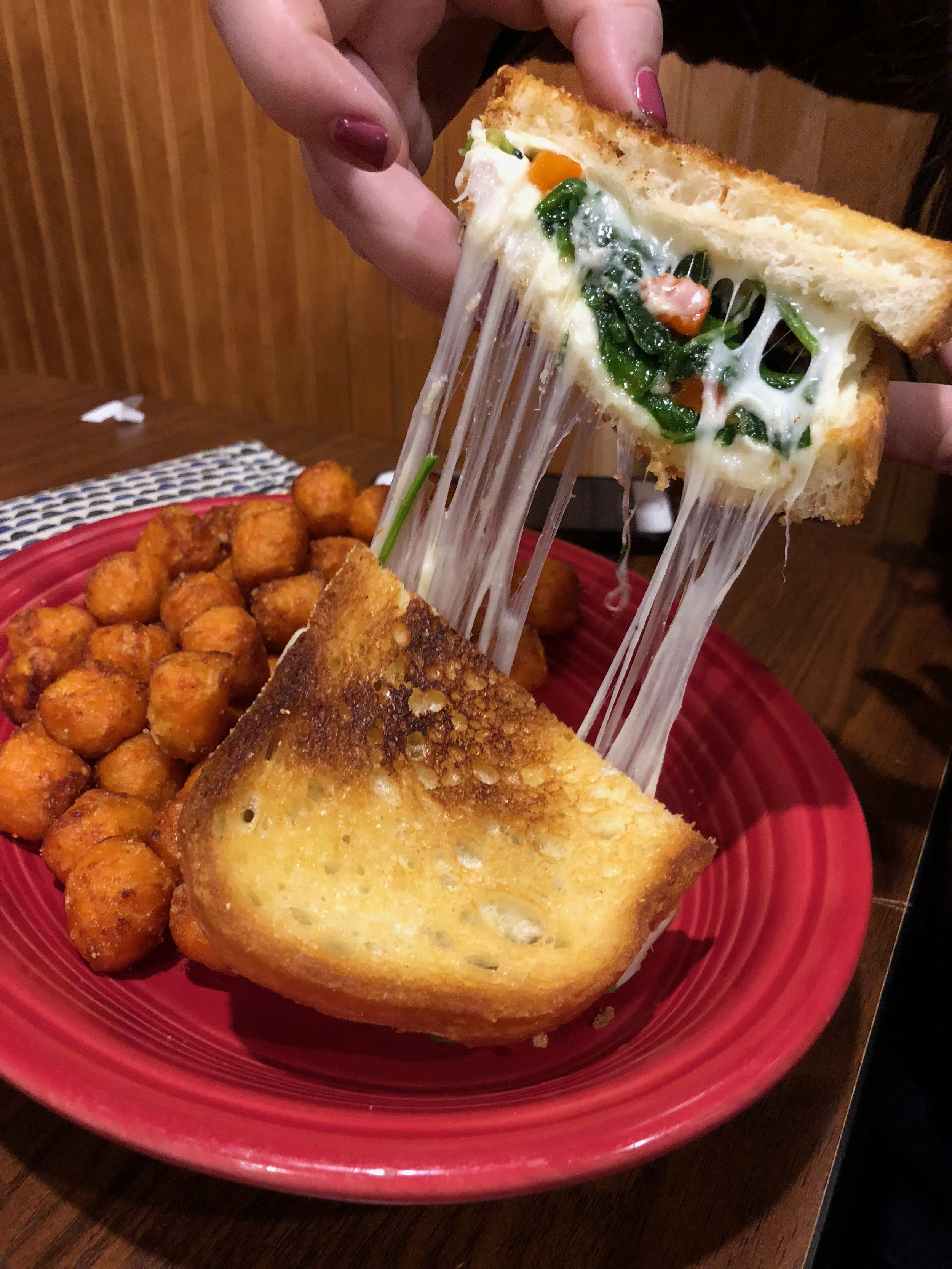 Crabby Grilled Cheese - A grilled cheese sandwich with a crab cake, wilted garlic spinach, roasted red peppers, and provolone cheese with sweet potato tots