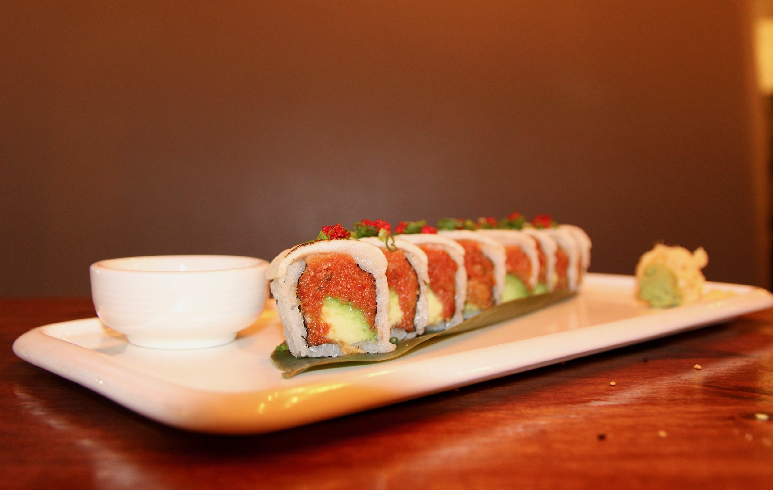 Marilyn Monroll made of spicy tuna, spicy salmon, avocado, torched white tuna, tobiko, and scallions