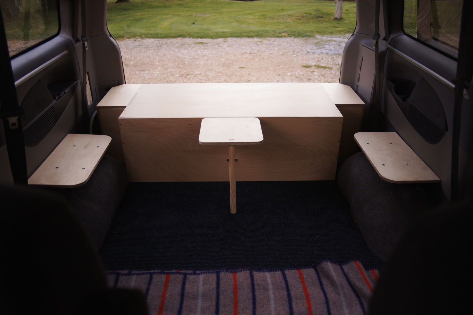 Inside the van, wheel arch mounted seats and the small folding table.
