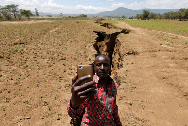 a-man-takes-a-selfie-photograph-near-a-chasm-suspected-to-have-been-caused-by-a-heavy-downpour-along-an-underground-fault-line-near-the-rift-valley-town-of-mai-mahiu-kenya-march-28-2018-picture-taken-march-28-201.jpg