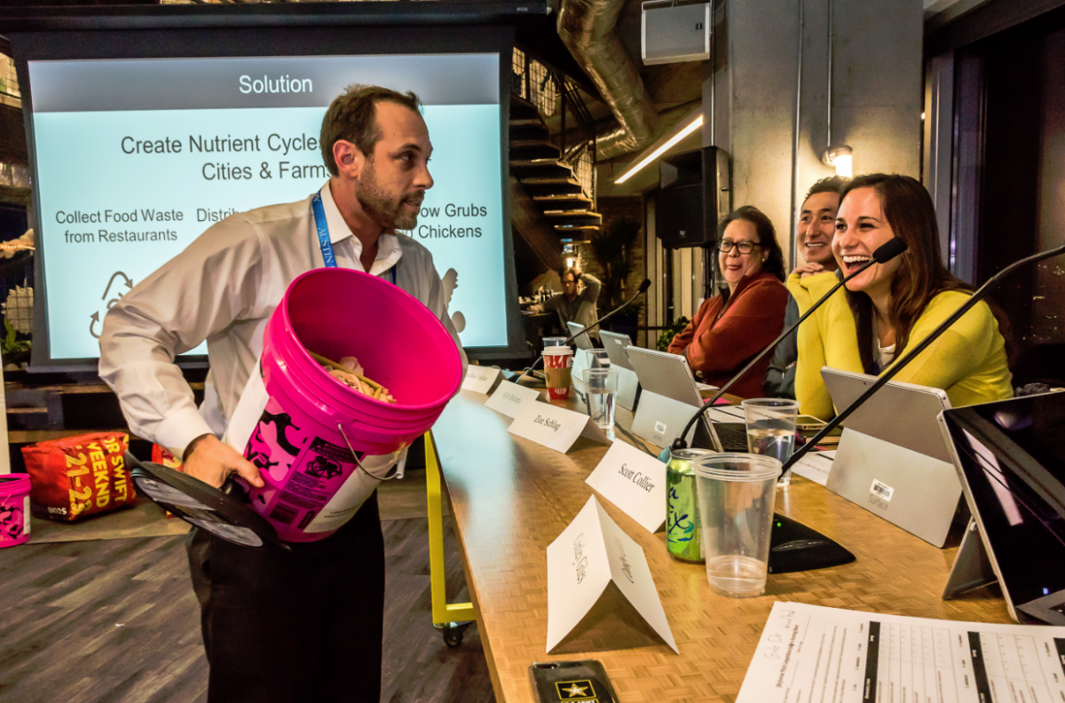 Robert Olivier of GrubTubs shows a sample food scrap collector to the 2016 [Re]verse Pitch judges. Judges pictured, from front to back: Zoe Schlag, Kyle Ballarta, and Rosa Rios Valdez.
