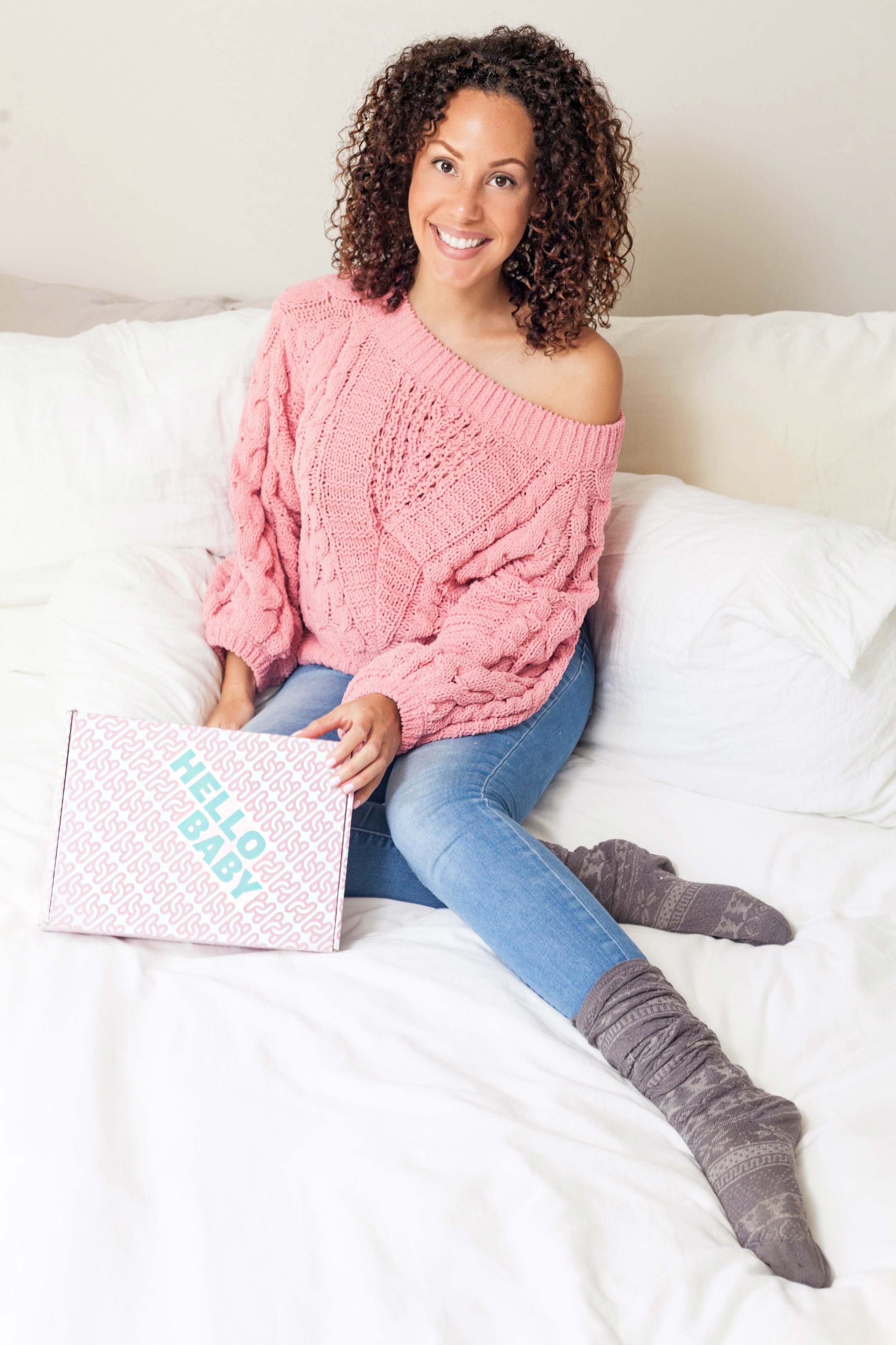 Mother with her Healthiest Baby Box sitting on a bed.