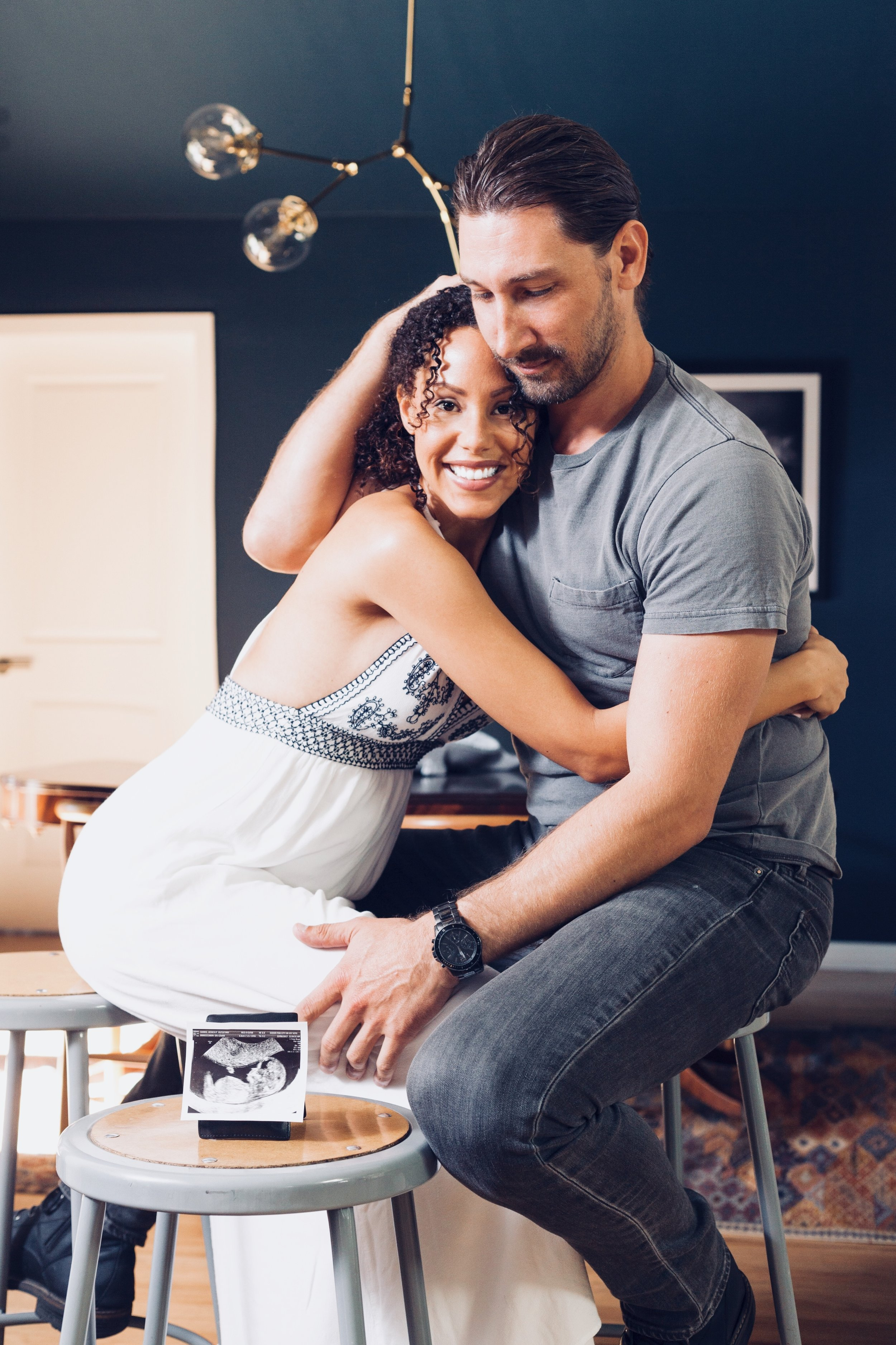 WOman and man embracing in front of an ultrasound sitting on benches.