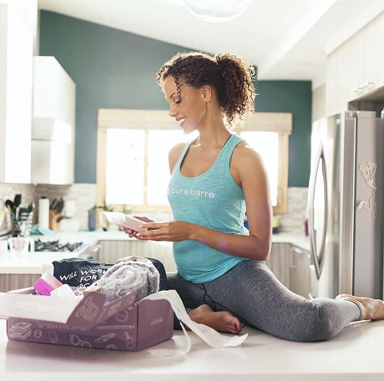 Woman looking at products from her FabFitFun subscription box a woman-owned company.
