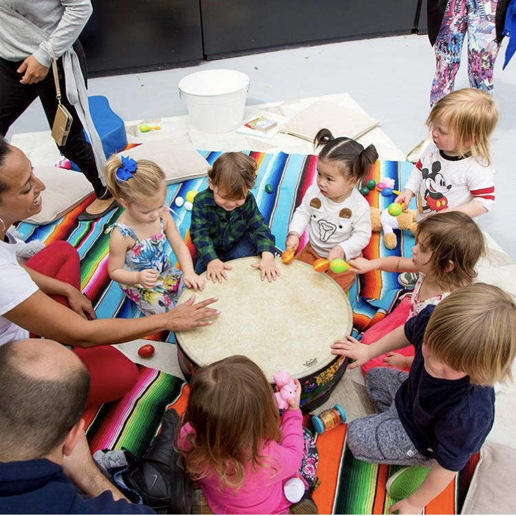 a group of small children playing a large drum