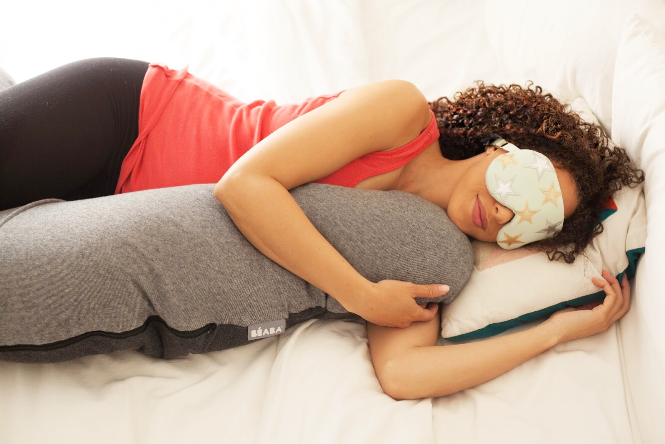 woman sleeping with a grey Flopsy pillow