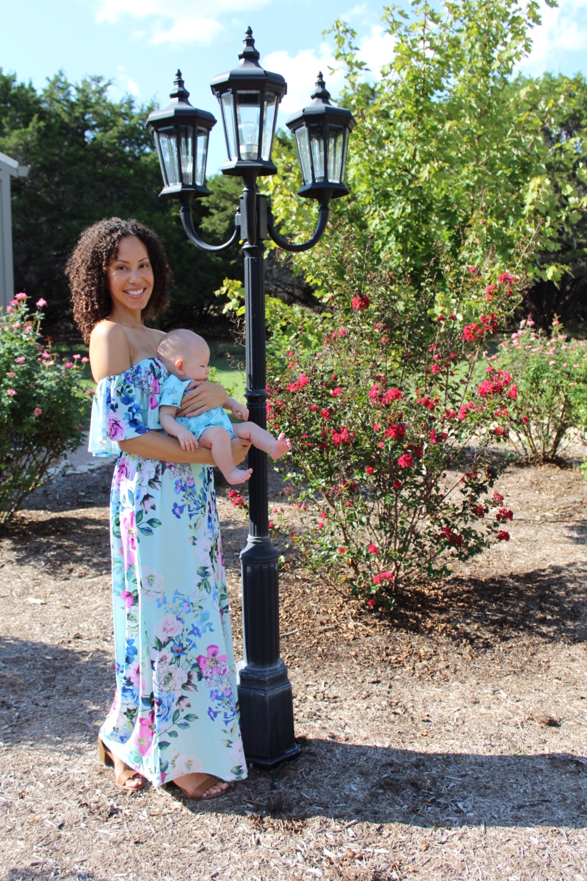 darkhaired woman holding baby in blue flowered dress next to a rose bush