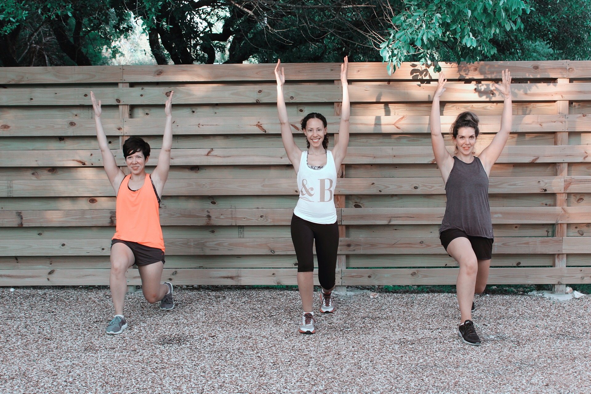 Three woman doing exercise stretches in front of a wooden fence