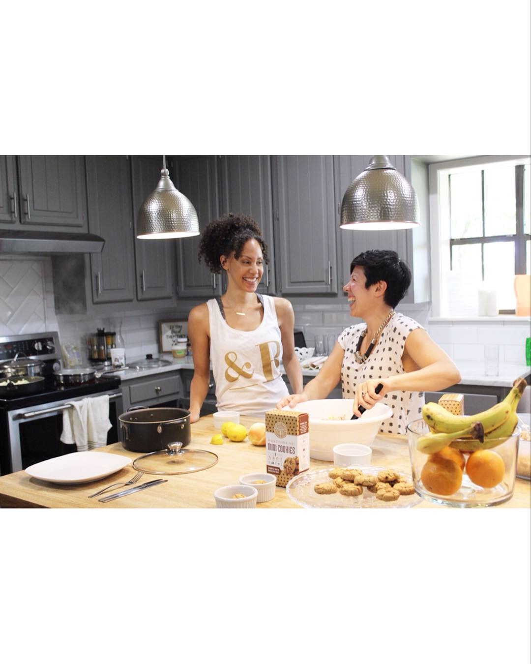 two darkahired women cooking in a kitchen with grey cabinets