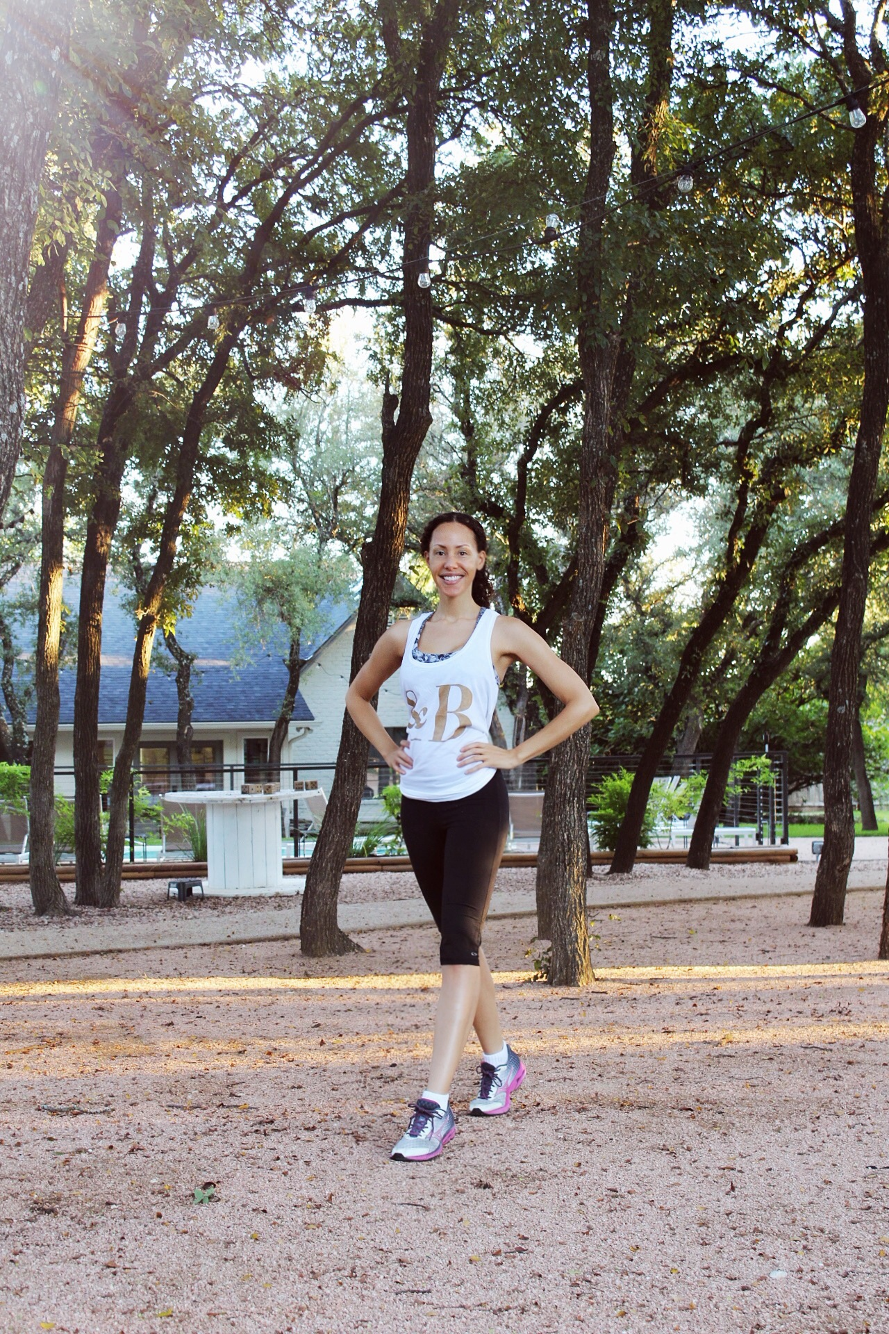 darkhaired woman in a white &Breathe tank top and black cropped leggings in front of trees