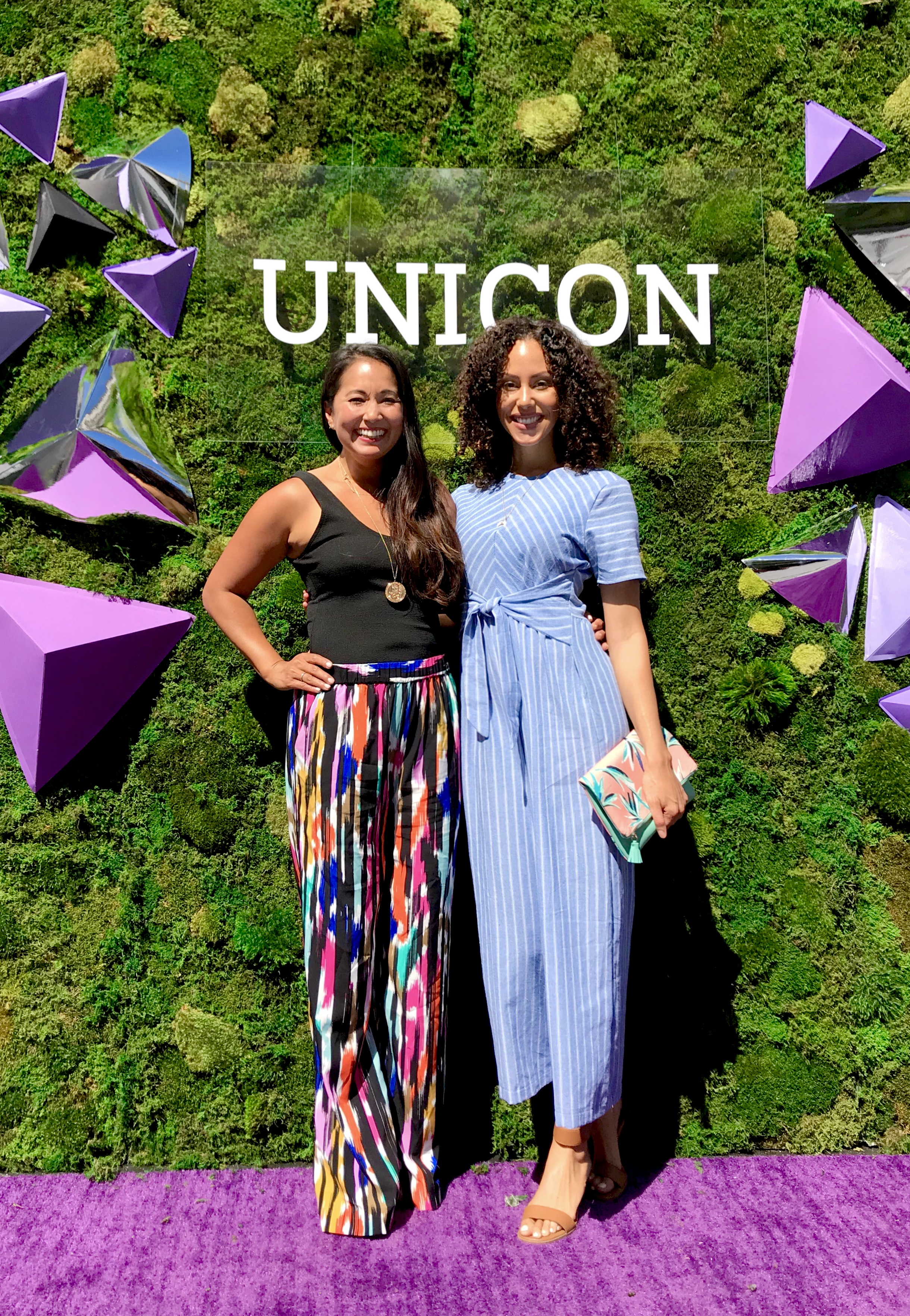 Two women dressed in colorful unicorn inpsired clothing standing in front of the Unicon backdrop