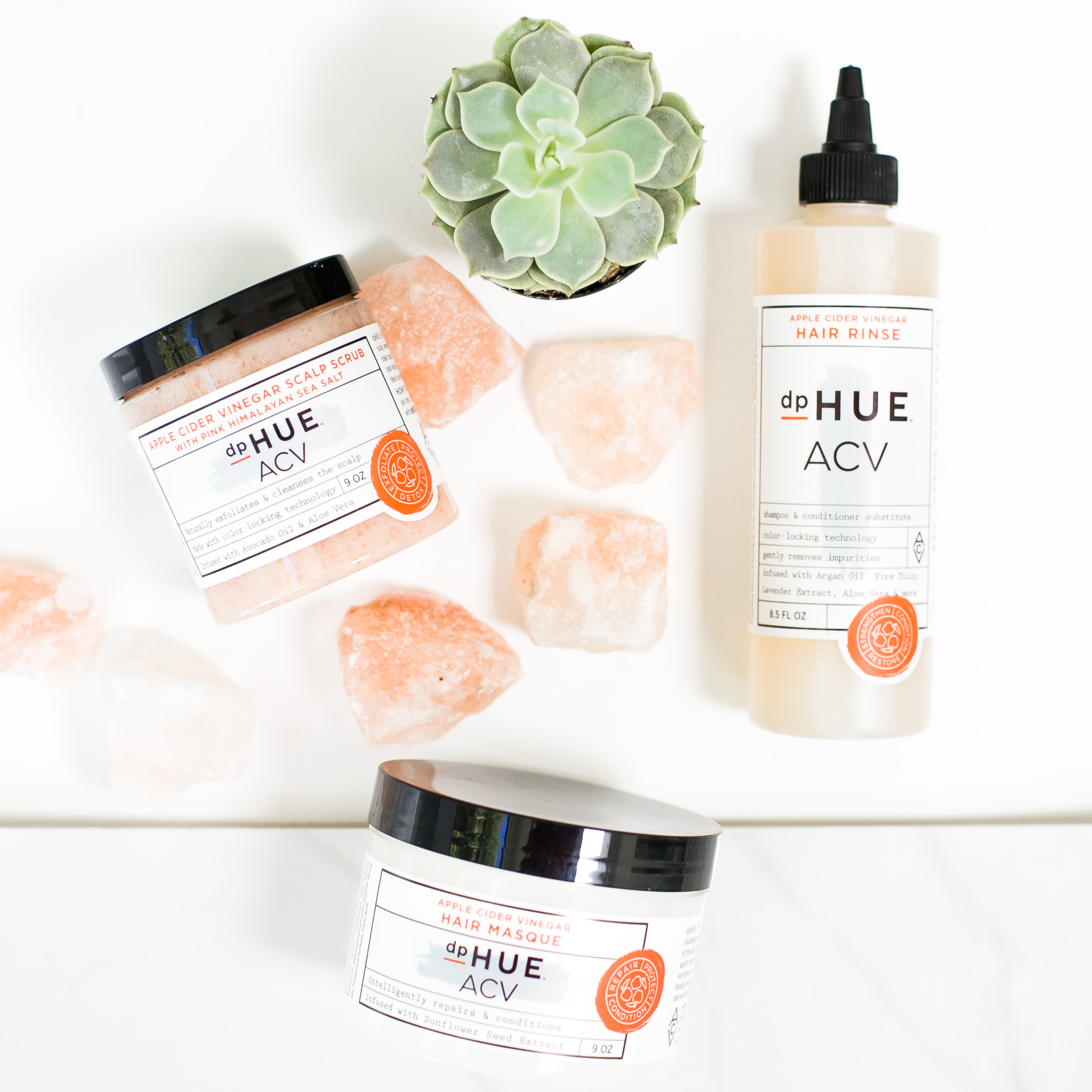 DP Hue Apple cider vinegar scalp scrub in a tub, hair rinse in a squeeze bottle and hair masque in a tub against a white background