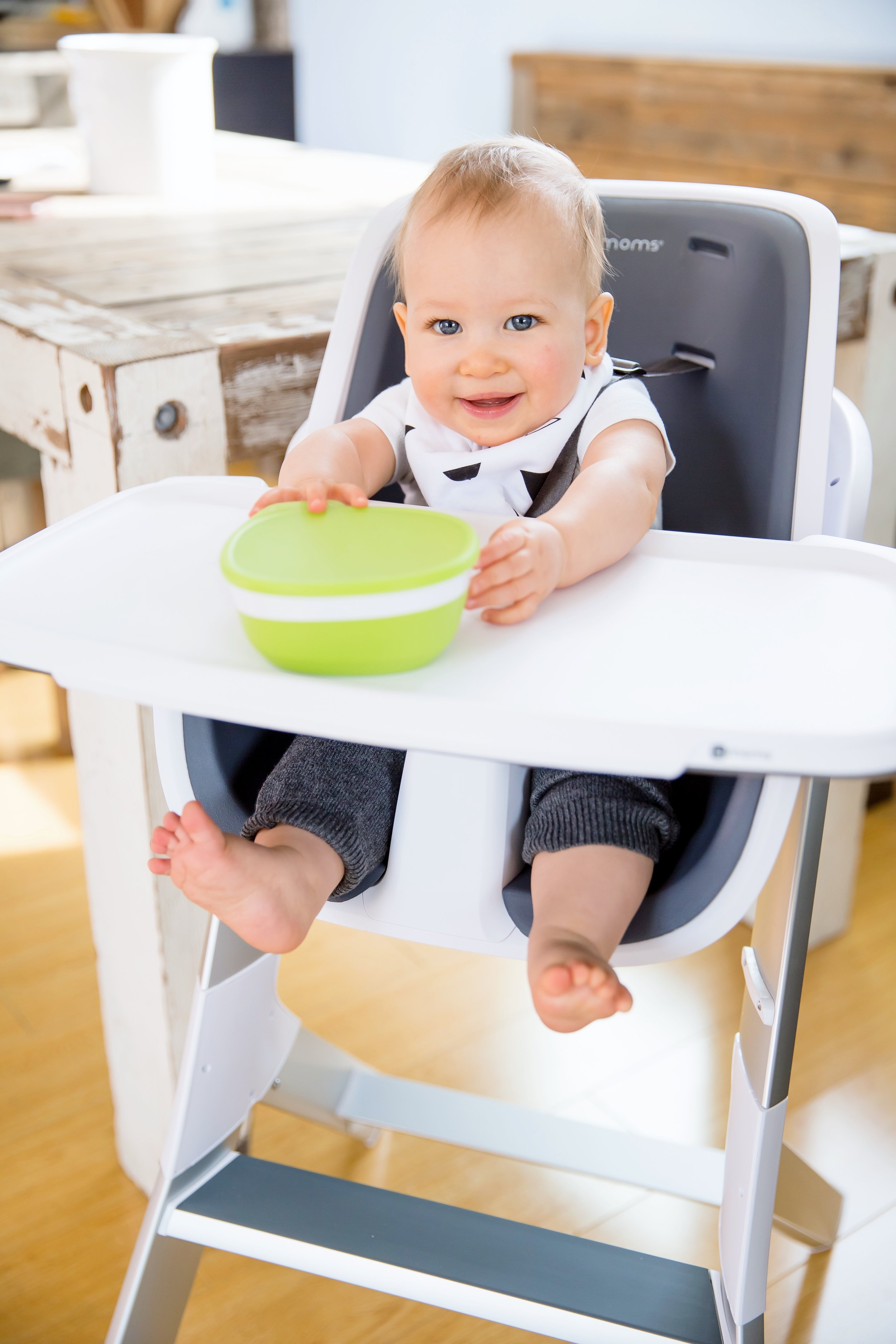 Baby sitting in a greay and white 4Moms High Chair
