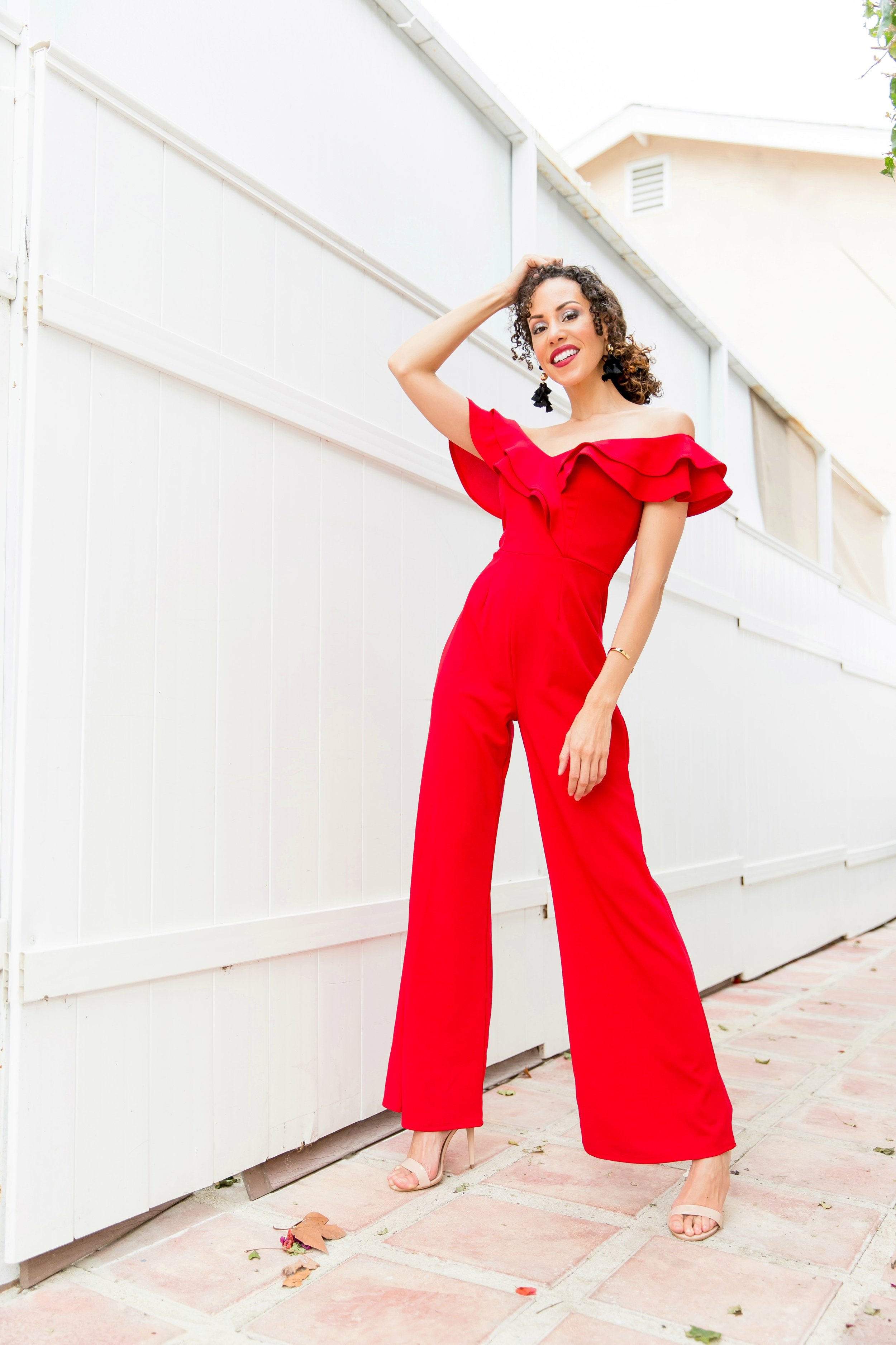 Woman in a red, ruffled jumpsuit in front of a tall white fence