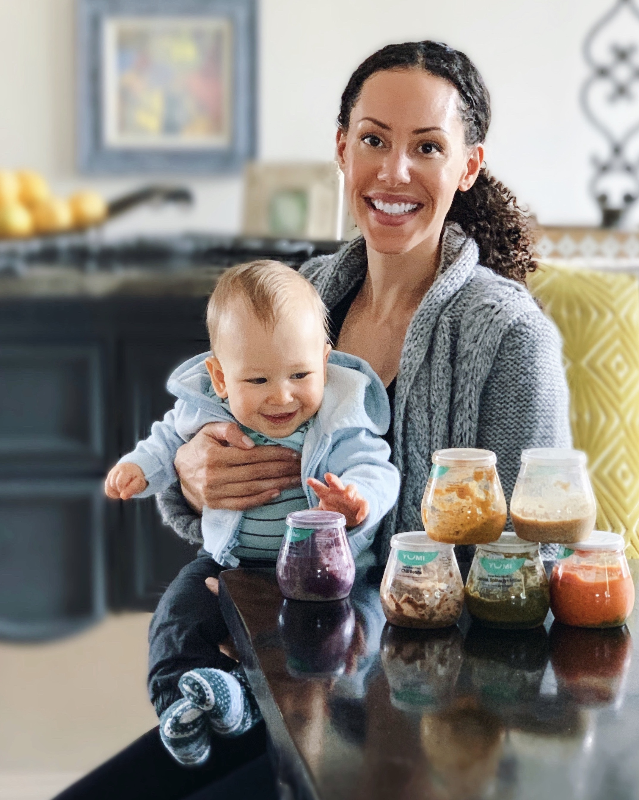 Mother and happy baby sitting at a table with Yumi Baby Food containers