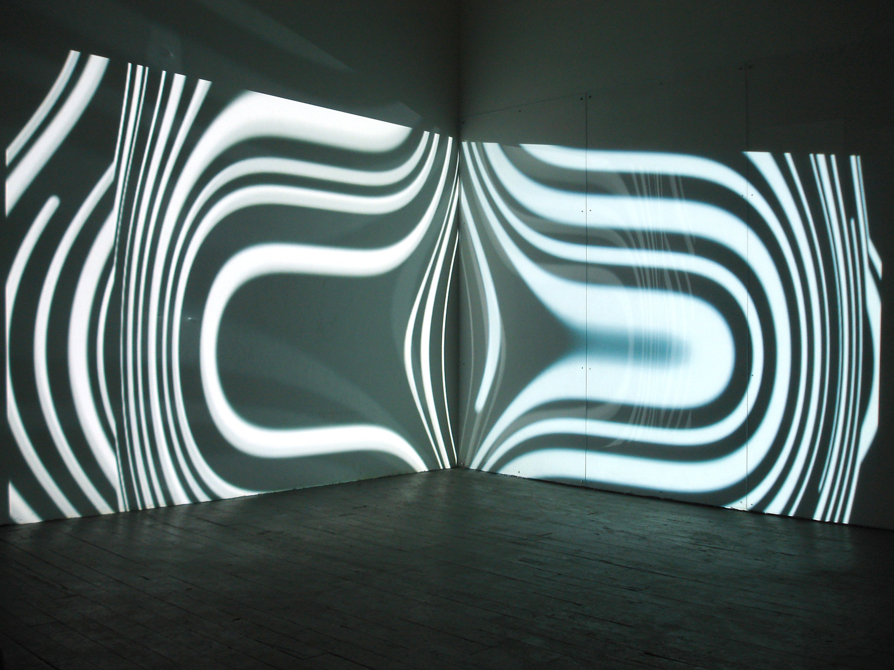 On Center, 2008,00:10:00 minute loop,color, no audio,h 9 x l 10 x w 12 feet,two video projections, plexiglass