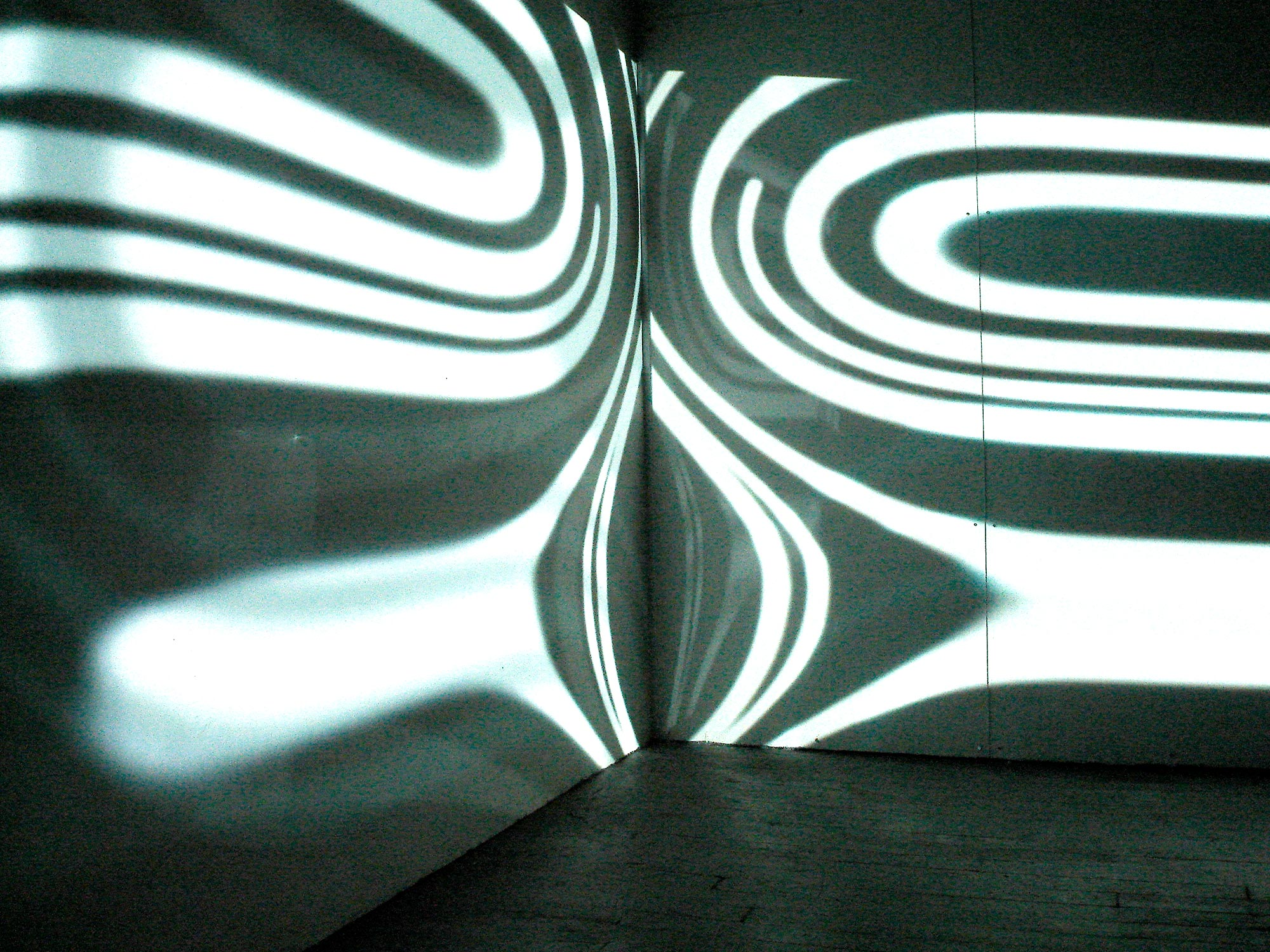 On Center, 2008, 00:10:00 minute loop, color, no audio, h 9 x l 10 x w 12 feet, two video projections, plexiglass