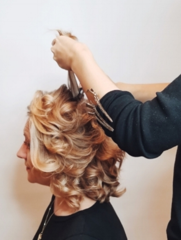 3. Create Volume - For more drama and flair, take small horizontal subsections, spray the roots with Control Force Firm Hold Hairspray and backcomb with a Teasing Comb. Focus on the crown and on the side of the head which will have all of the cascading curls. *Feel free to take a super deep side part for an even edgier look.*