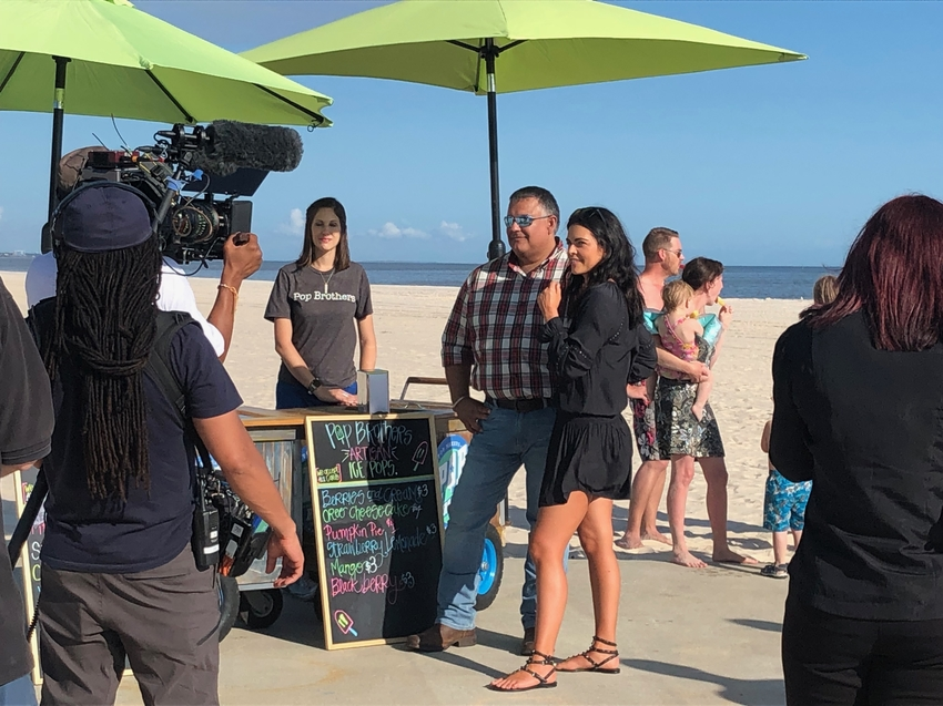 Katie Lee poses for a photo on the beach with Pop Brothers owner Octavio.jpeg