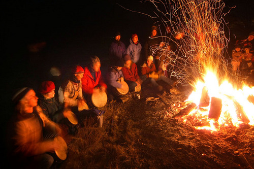 t12.21.09 Bob King -- kingSOLSTICE1222c -- Participants at the Winter Solstice celebration held near the Two Harbors lighthouse Monday night sit around a bonfire while they drum in the new season. Today is the first full day of winter.