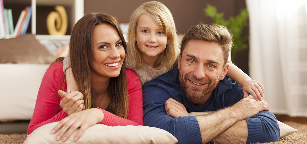Family Laying on Floor with child on back of parents