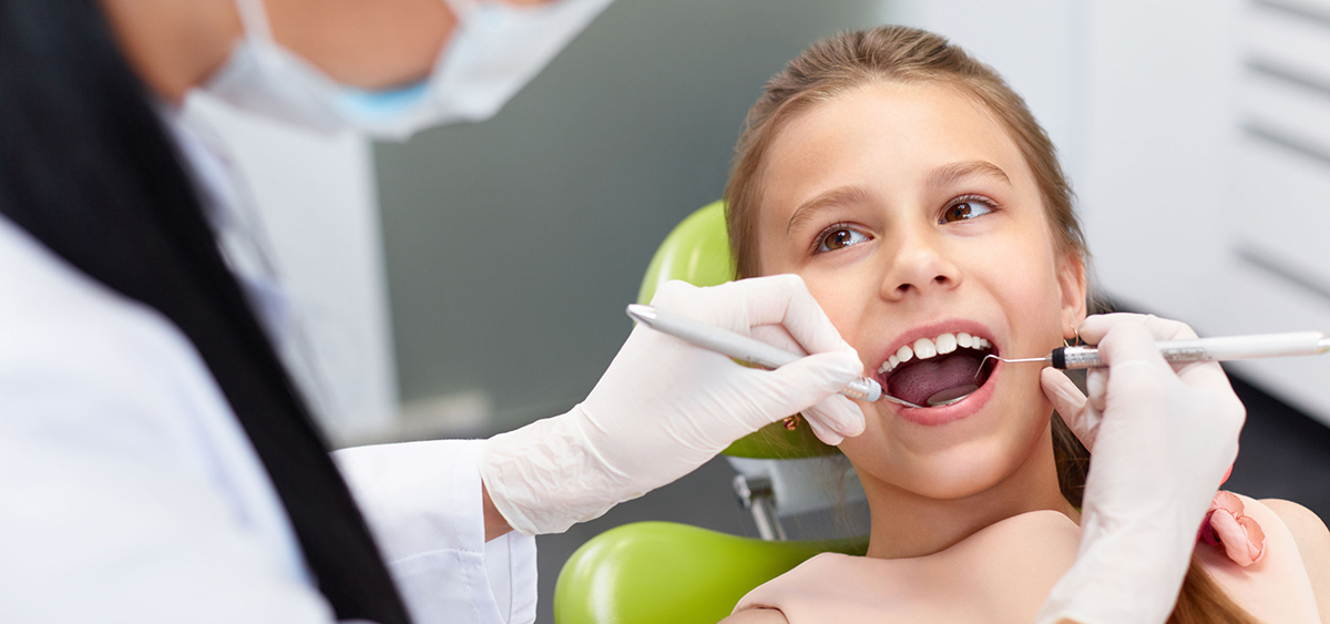 Child looks at doctor while getting teeth cleaned