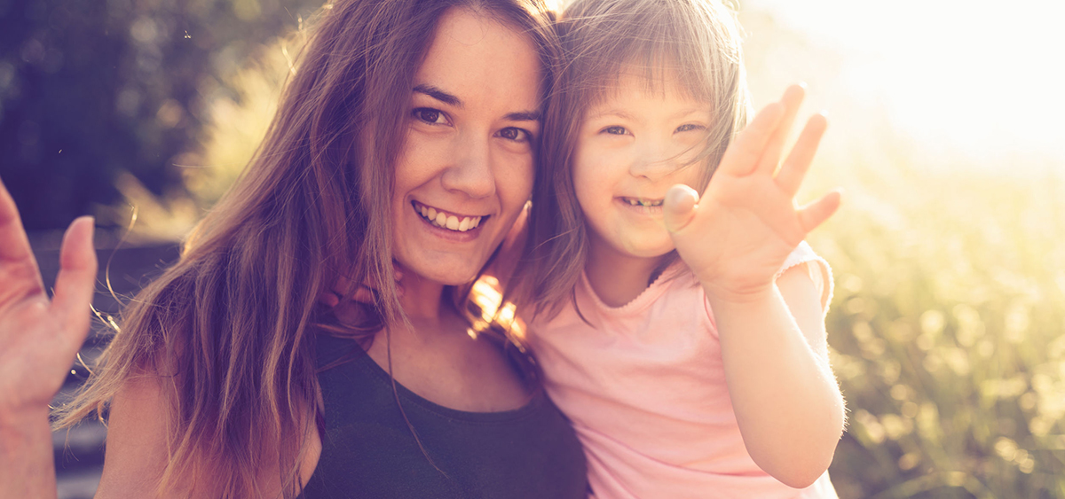 Mother and down syndrome daughter waving at camera.