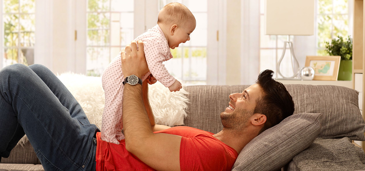 Man holding a laughing baby on his chest lying down