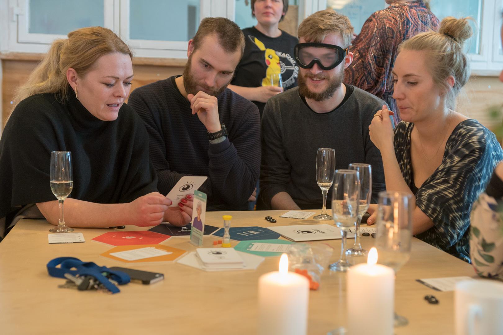 Gæsterne sidder rundt om et bord og spiller læringsspillet Indsigt