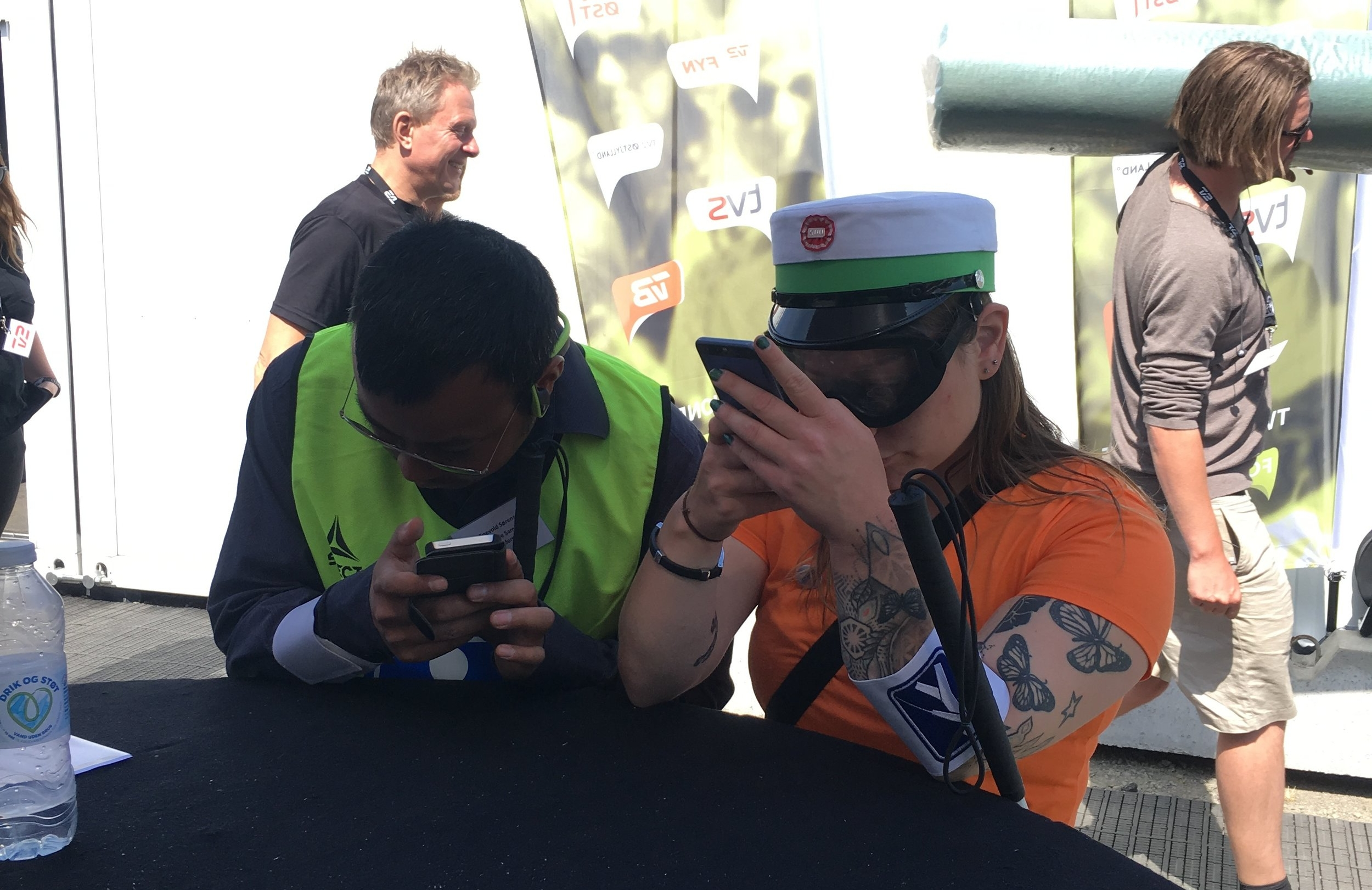Test af Folkemødets digitale tilgængelighed. Her er det Folkemødets app, der bliver undersøgt med brug af blandt andet Ballasts simulationsbriller, Perspectacles. De to deltagere i Tilgængelighedsstafetten løser stafetopgaven med at finde toiletter. To personer sidder bøjet over deres telefoner. Den ene - en mand - ser ud til at lytte til telefonen. Den anden - en kvinde - har simulationsbrillerne Perspectacles på og holder telefonen helt op foran ansigtet.
