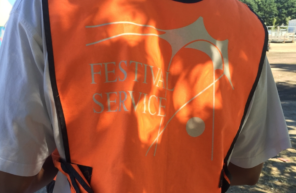 En frivillig fra Roskilde Festival med en orange vest på
