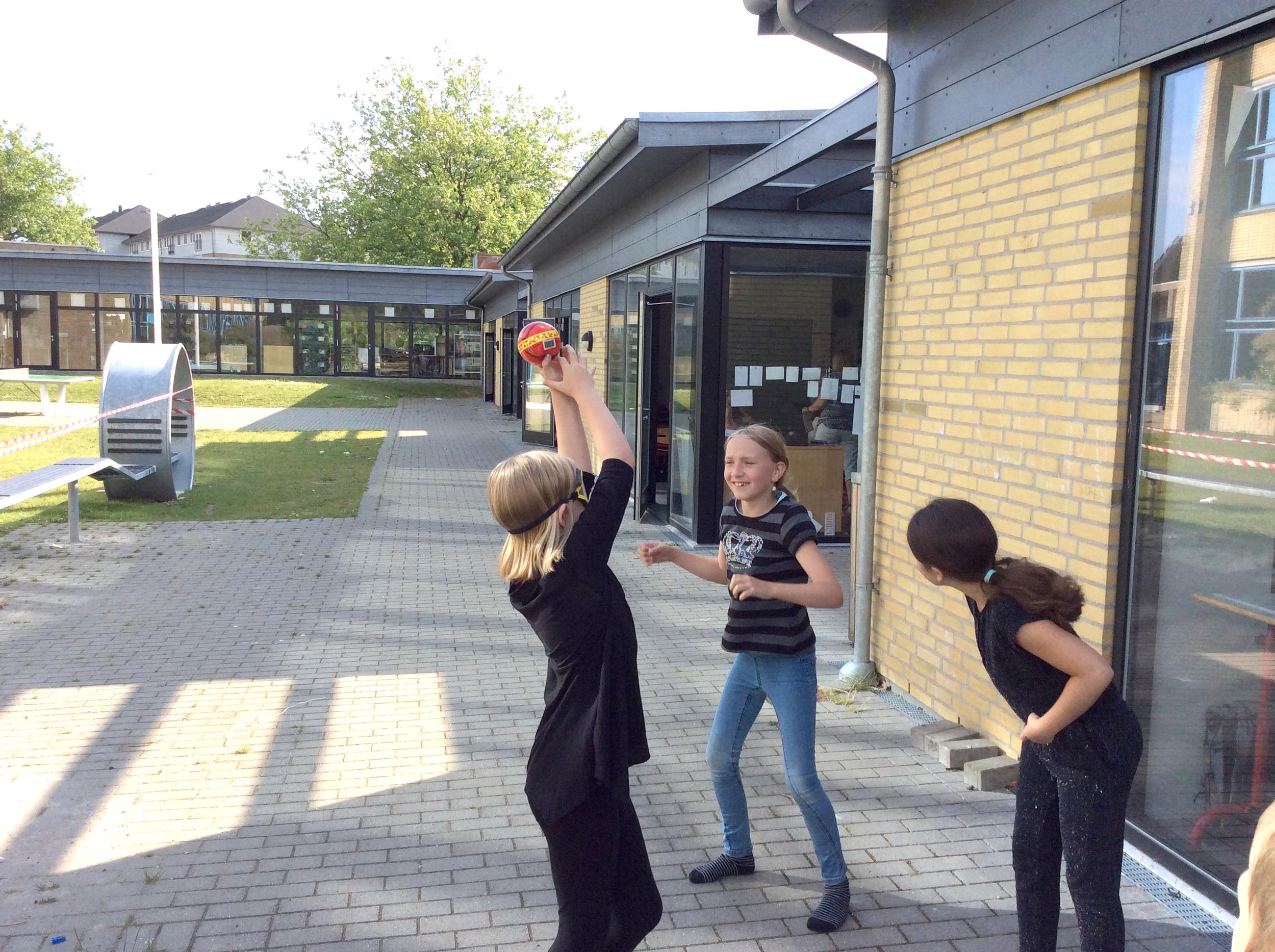 Tre skolebørn leger med en bold i skolegården