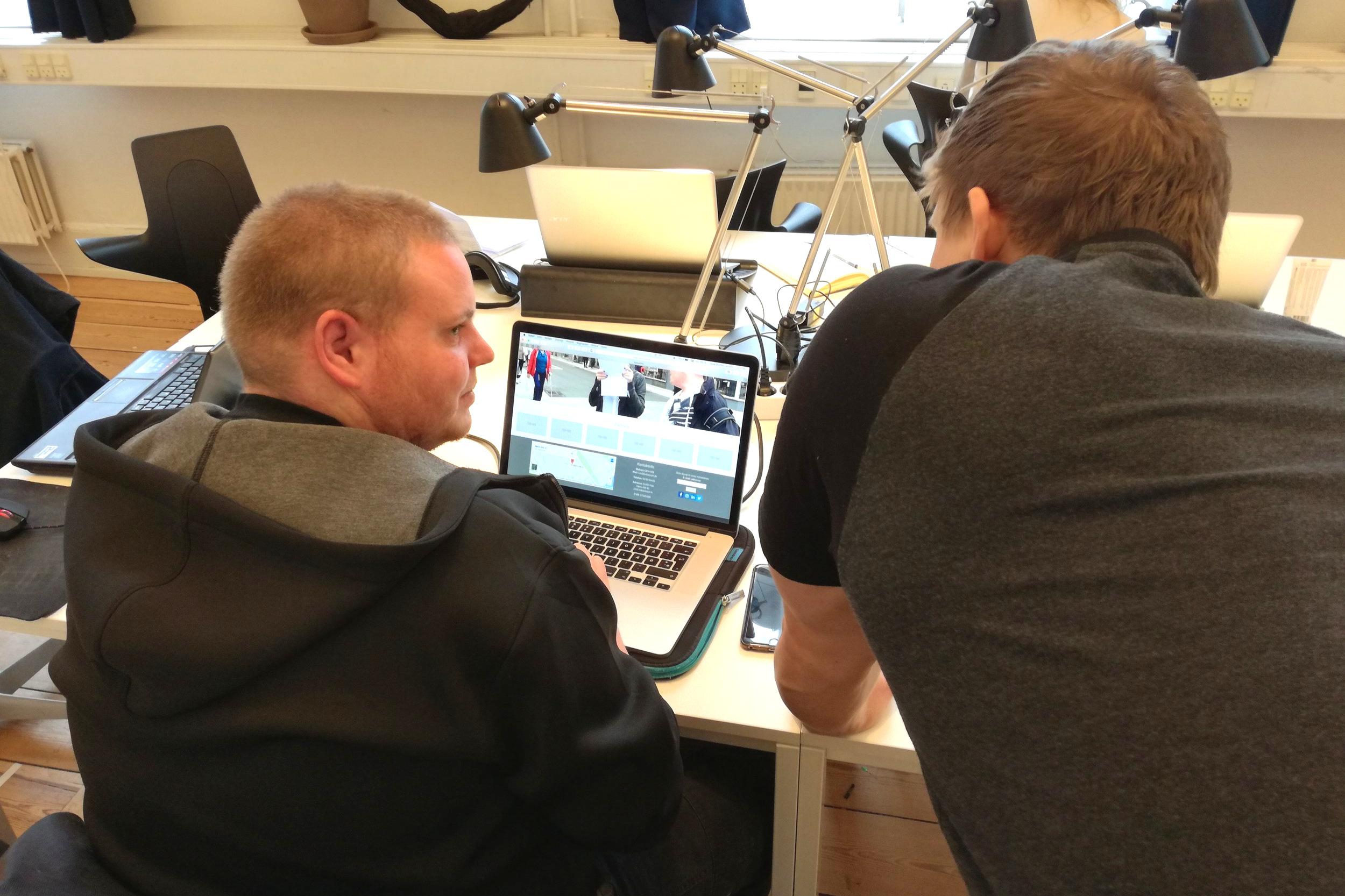 På billedet ses to mænd som tjekker en hjemmeside for tilgængelighed.