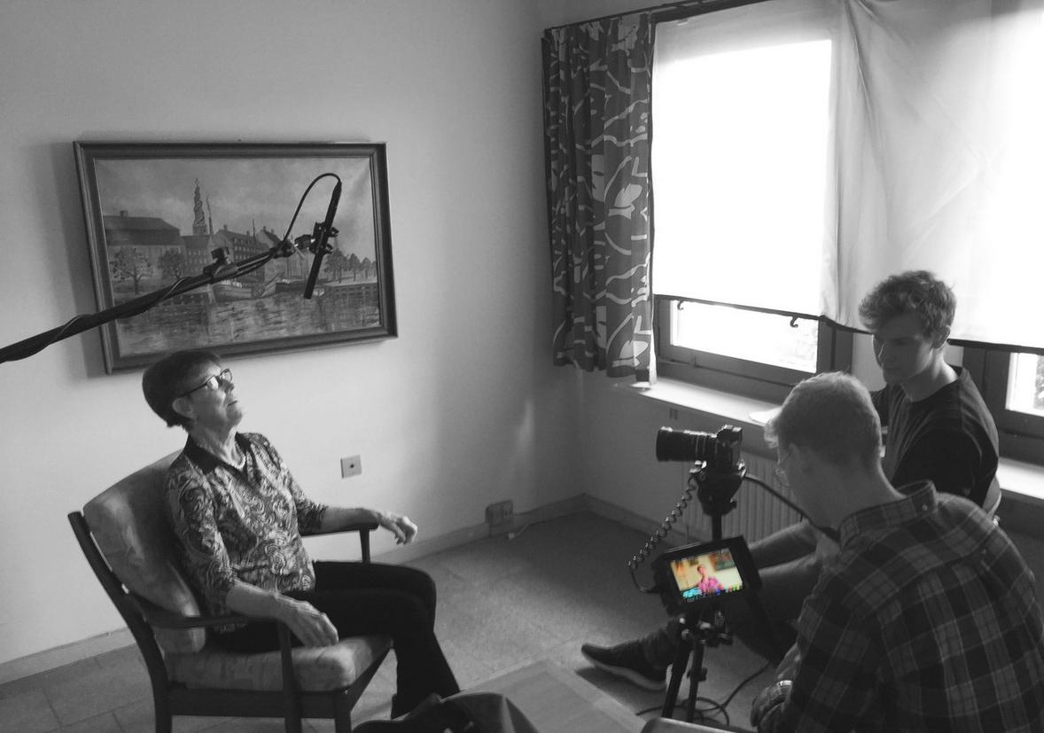 En kvindelig beboer på plejehjemmet Solterasserne bliver interviewet og filmet af to mandelige medarbejdere på projektet.