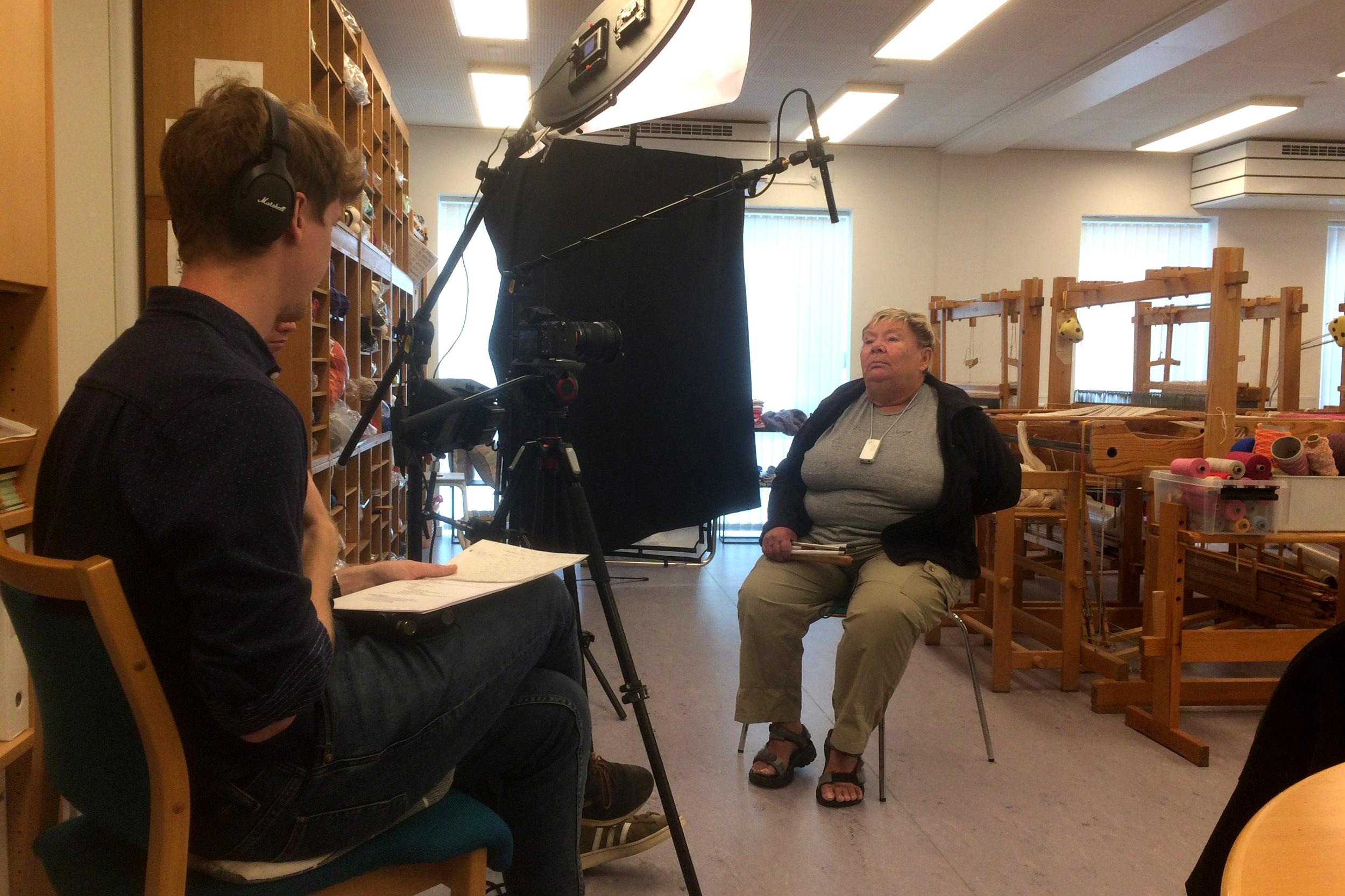 Her ses Birte, som er i gang med at blive interviewet af en mandlig projektmedarbejder. Interviewet finder sted blandt væve og garn i et aktivitetscenter.