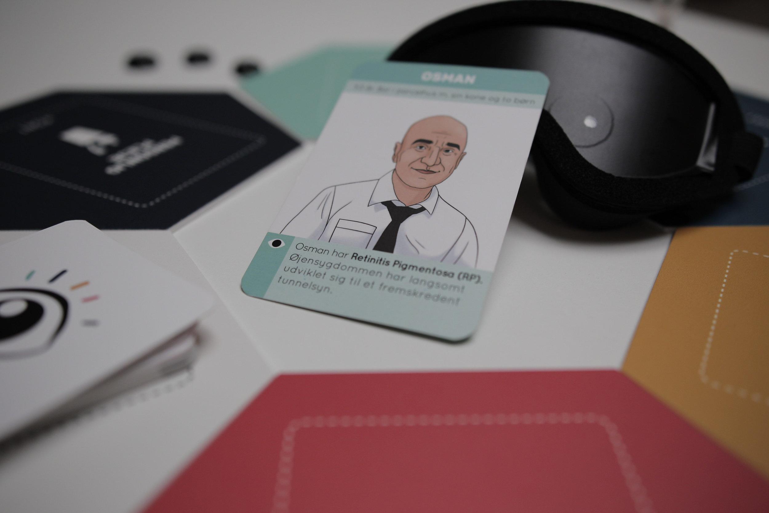 Her ses et zoomet billede af brætspillet Indsigt med hovedpersonen Osman i fokus. Ved siden af Osman-kortet ses spillepladerne, spillekortene og simulationsbrillen som simulerer Osmans tunnelsyn.