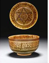Rare intact Syrian Tell Minis Lustre Pottery Bowl decorated in overglaze lustre, 11th – 12th Century, 16.4cm diameter, inscribed  'baraka'  in the centre